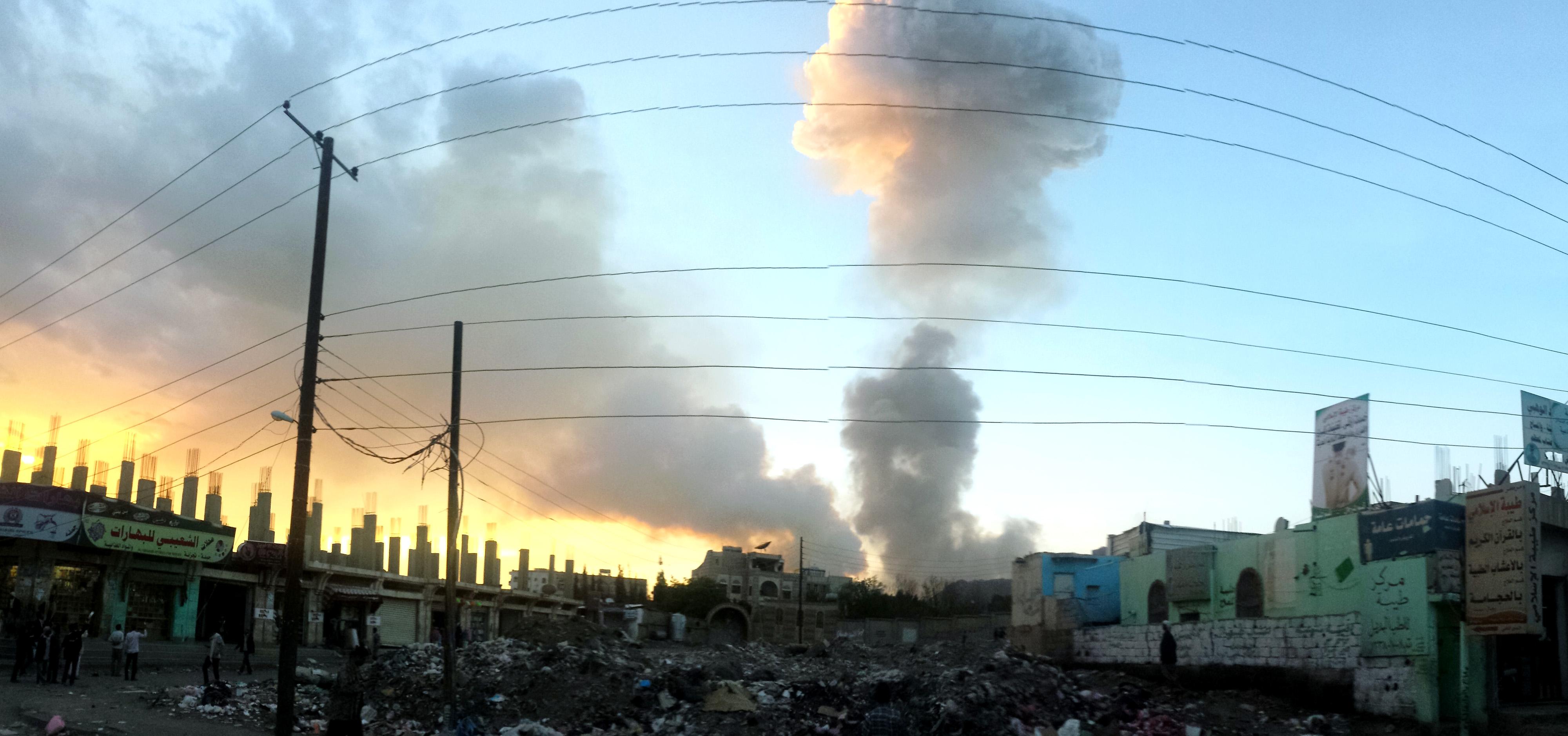 Luftangriff in Sanaa, Jemen, 5. November 2015: Ein Rauchpilz steigt im Hintergrund auf, im Vordergrund Trümmer und Ruinen von Häusern. aus