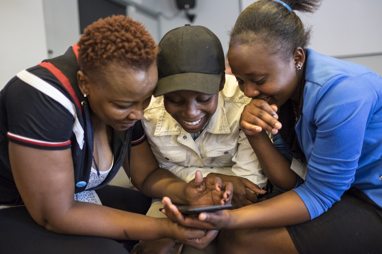 Drei Frauen nutzen ein Smartphone.