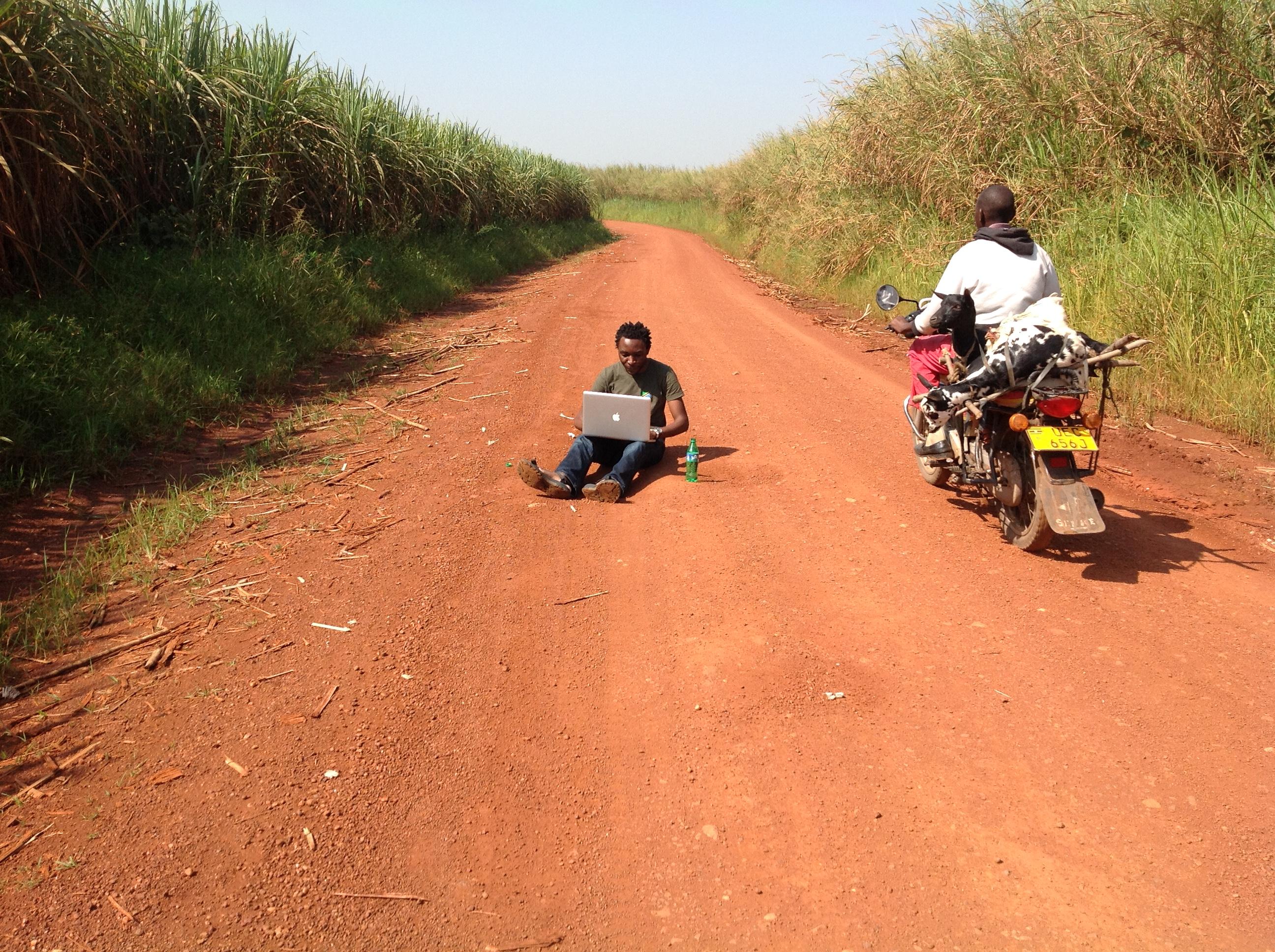 Jude Mukundane, Teilnehmer an digitalen Projekten der DW Akademie in Uganda, startete ein Experiment: Wie lange kann man mitten auf dieser einsamen Straße im Masindi-Distrikt am Computer arbeiten, bevor der Verkehr einen vertreibt? Nach 30 Minuten gab Mukundane auf.