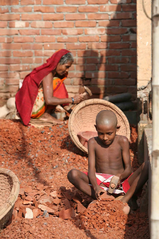 Ein Junge in Dhaka in Bangladesch stellt Backsteine her.