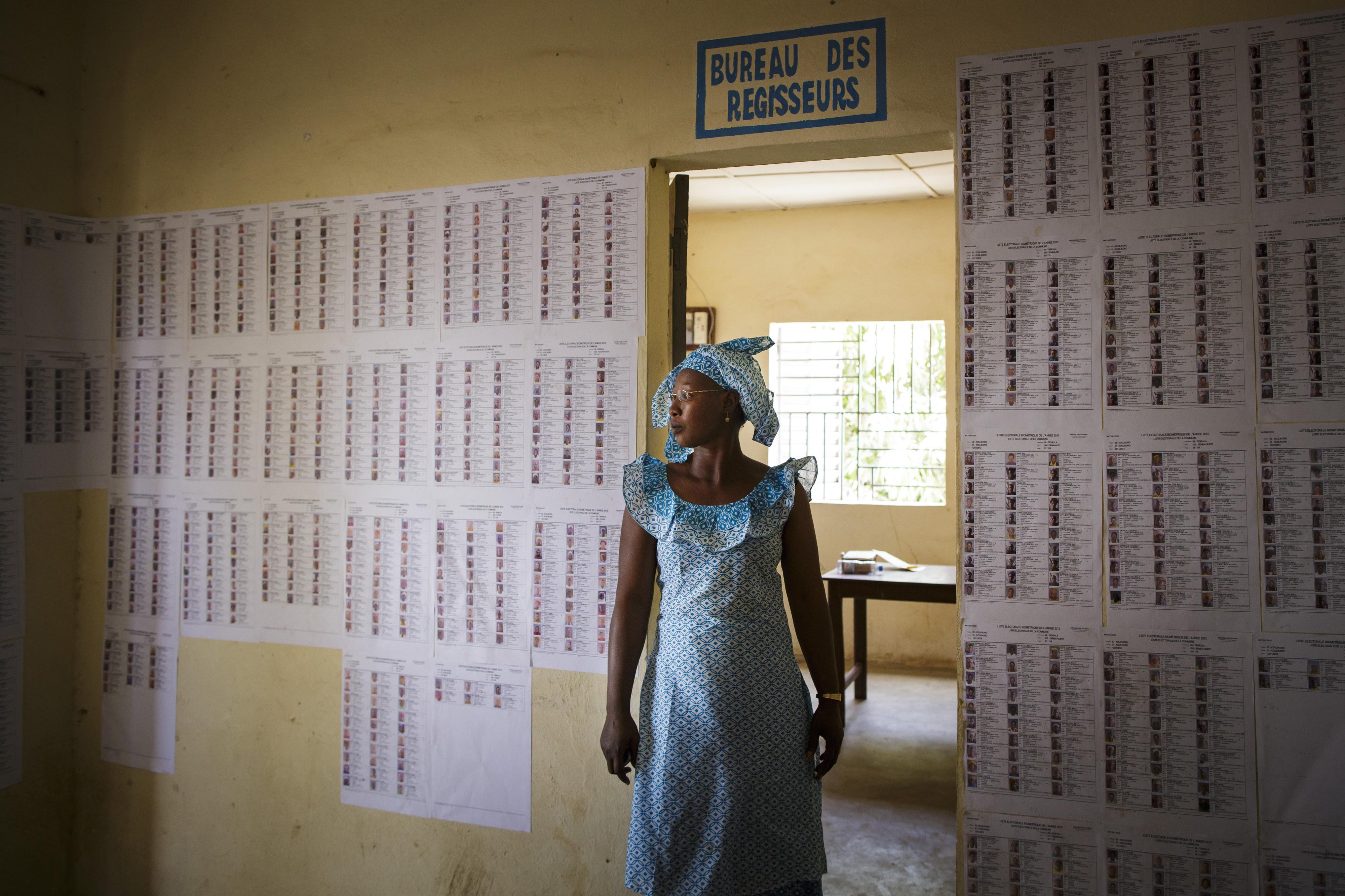 Eine Frau steht in der Gemeindeverwaltung von Tienfala in Mali vor Wahllisten.