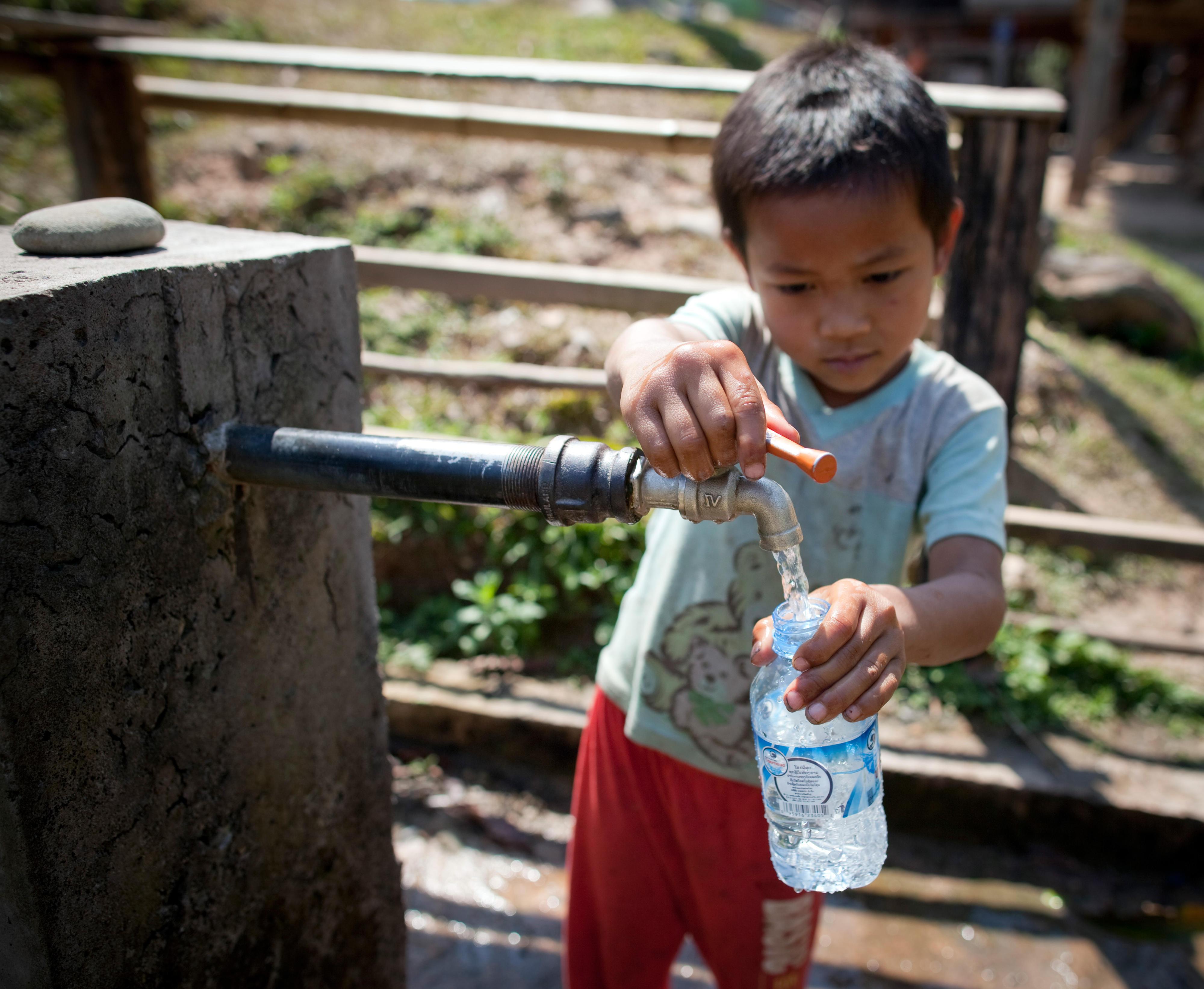 Ein Kind in Vieng Phouka, Laos, befüllt an einem öffentlichen Brunnen eine Flasche.