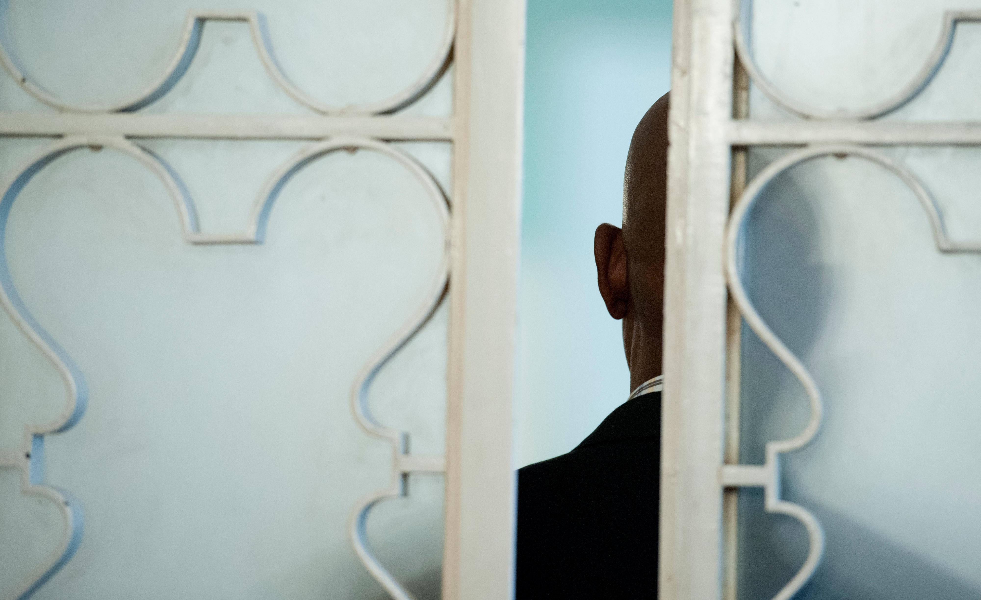 Durch einen Türspalt sieht man einen Mann von hinten.