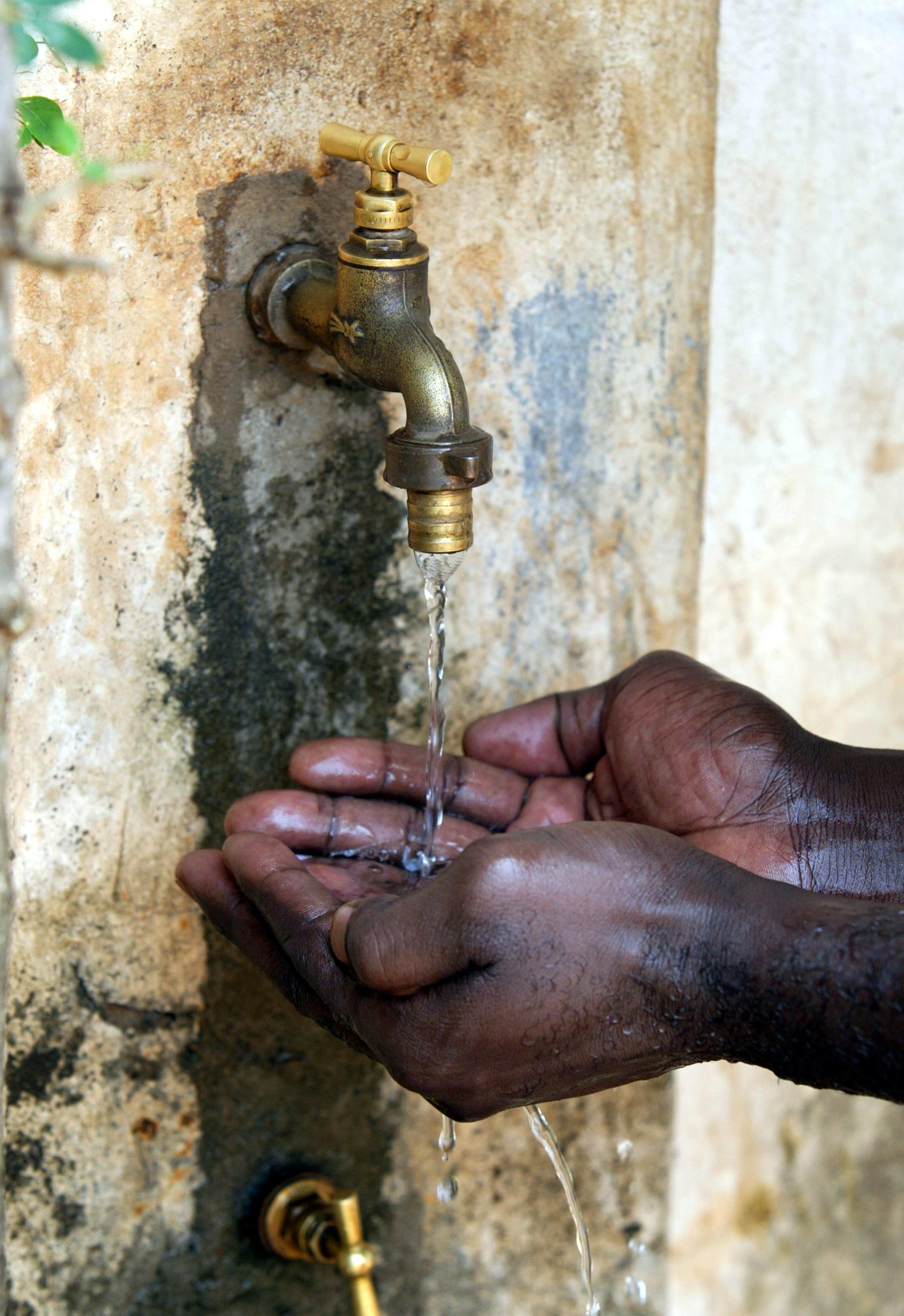 Hände unter einem Wasserhahn in Benin