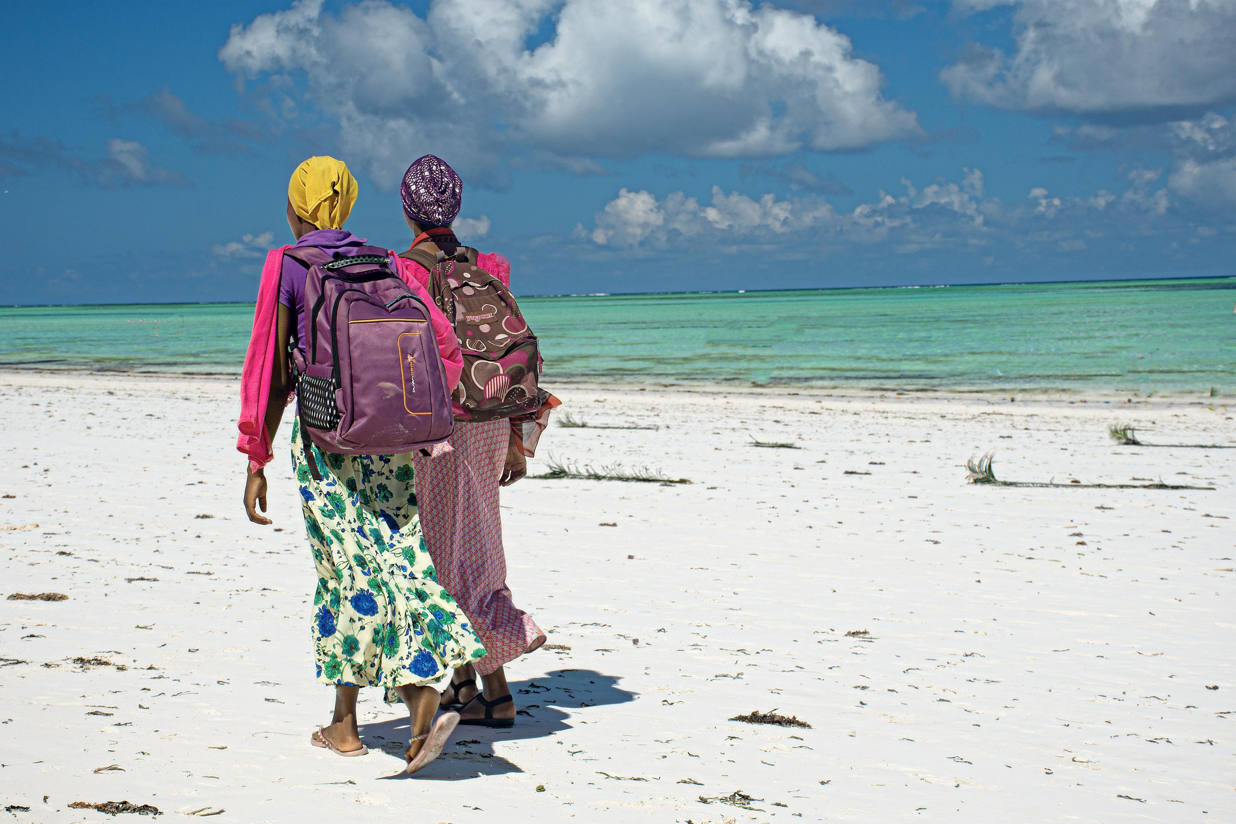 Schülerinnen auf ihrem Schulweg an einem Strand der zu Tansania gehörenden Insel Sansibar