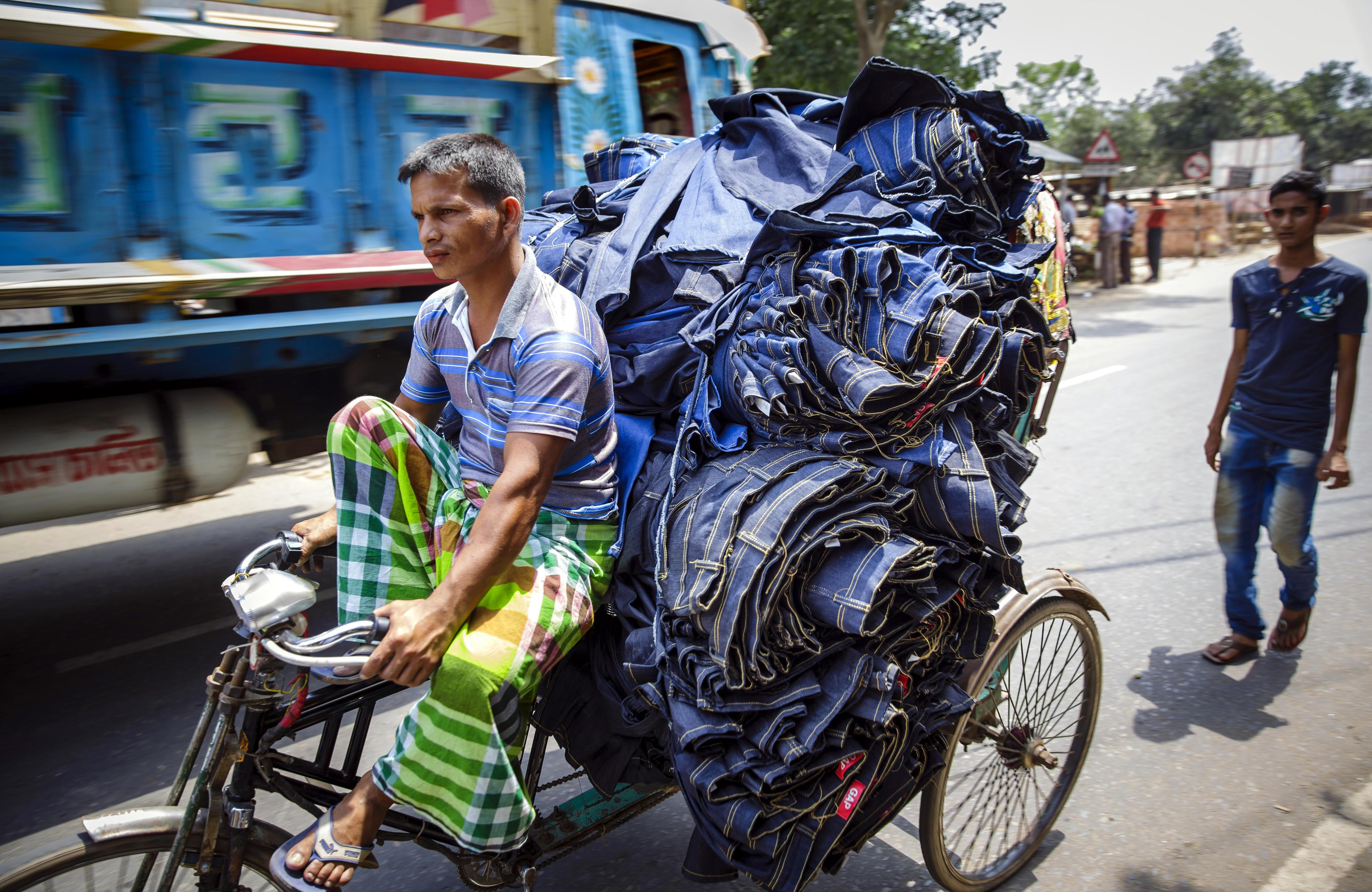 Ein Mann transportiert Jeans auf einer Rikscha