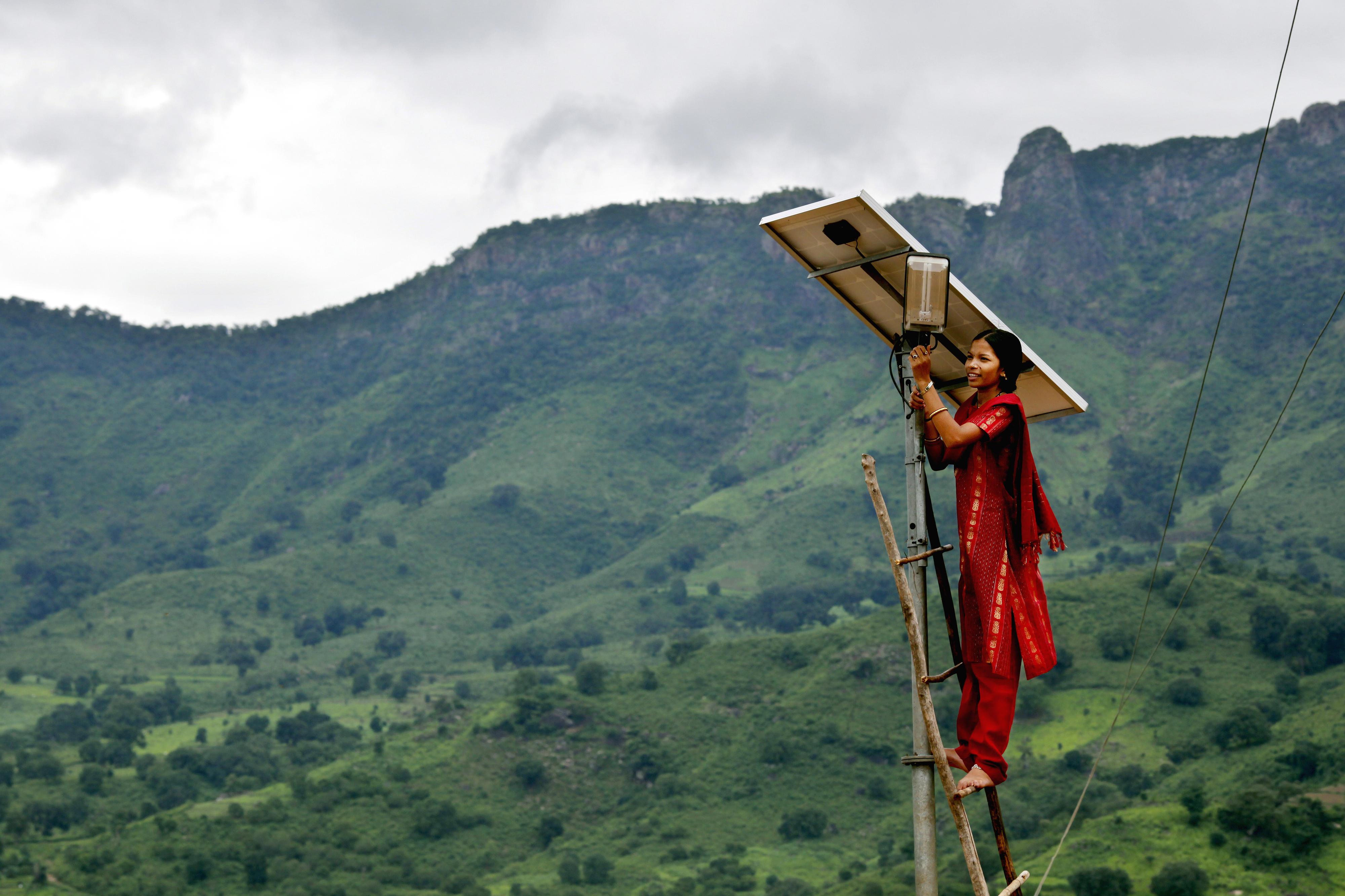 Eine Solaringenieurin überprüft eine solarbetriebene Straßenlaterne.
