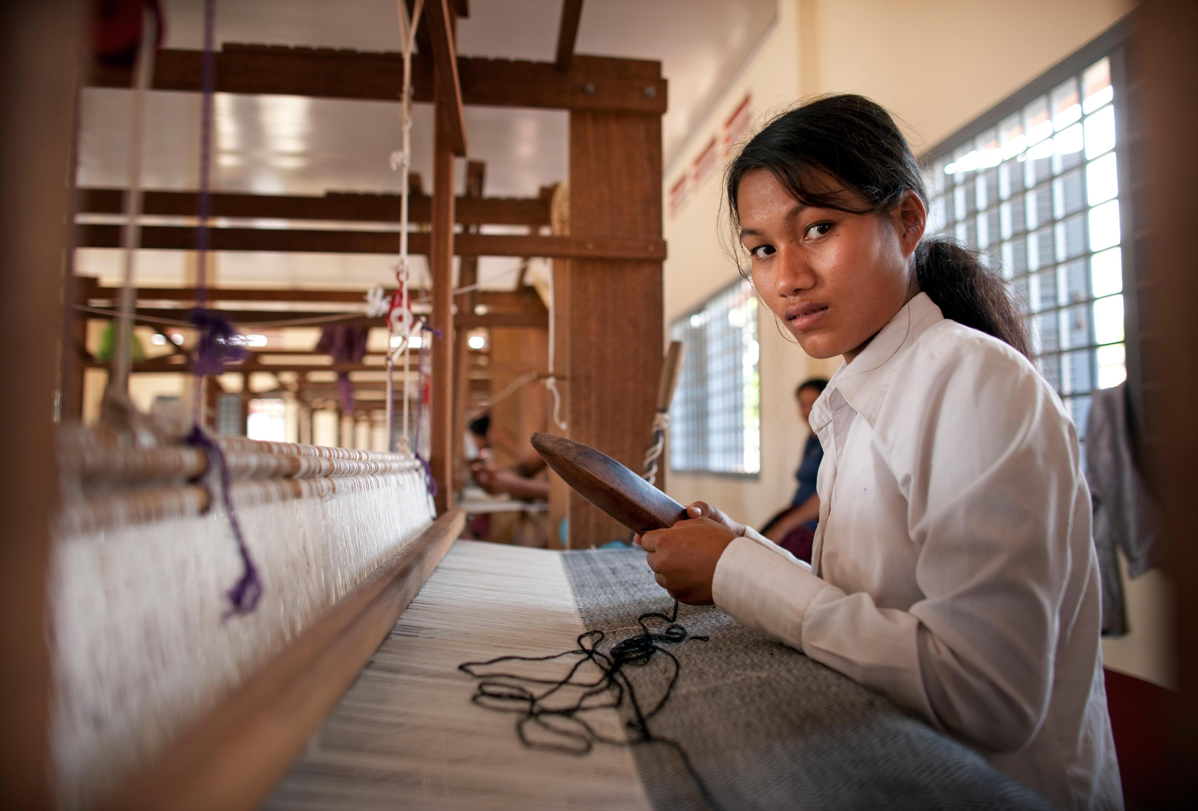 Eine Frau lernt, einen Webstuhl zu bedienen.
