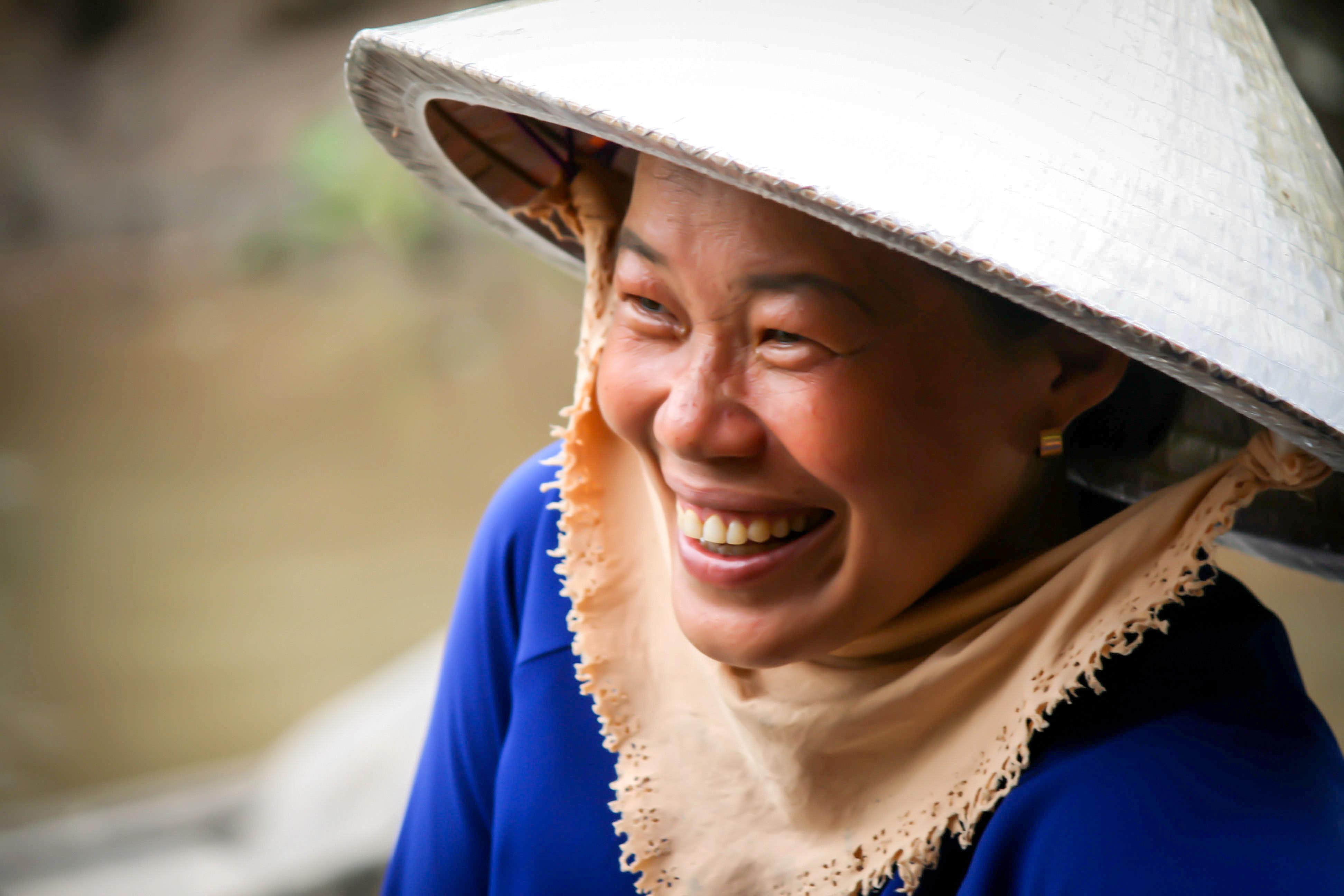 Eine lachende Frau mit Hut in Vietnam
