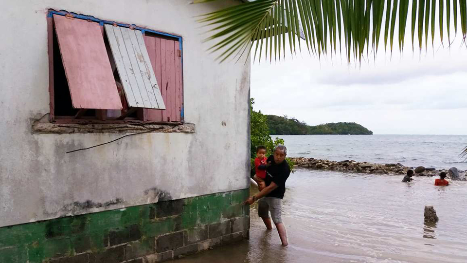 A man shows at his house in St. Lucia how high the last flood was.