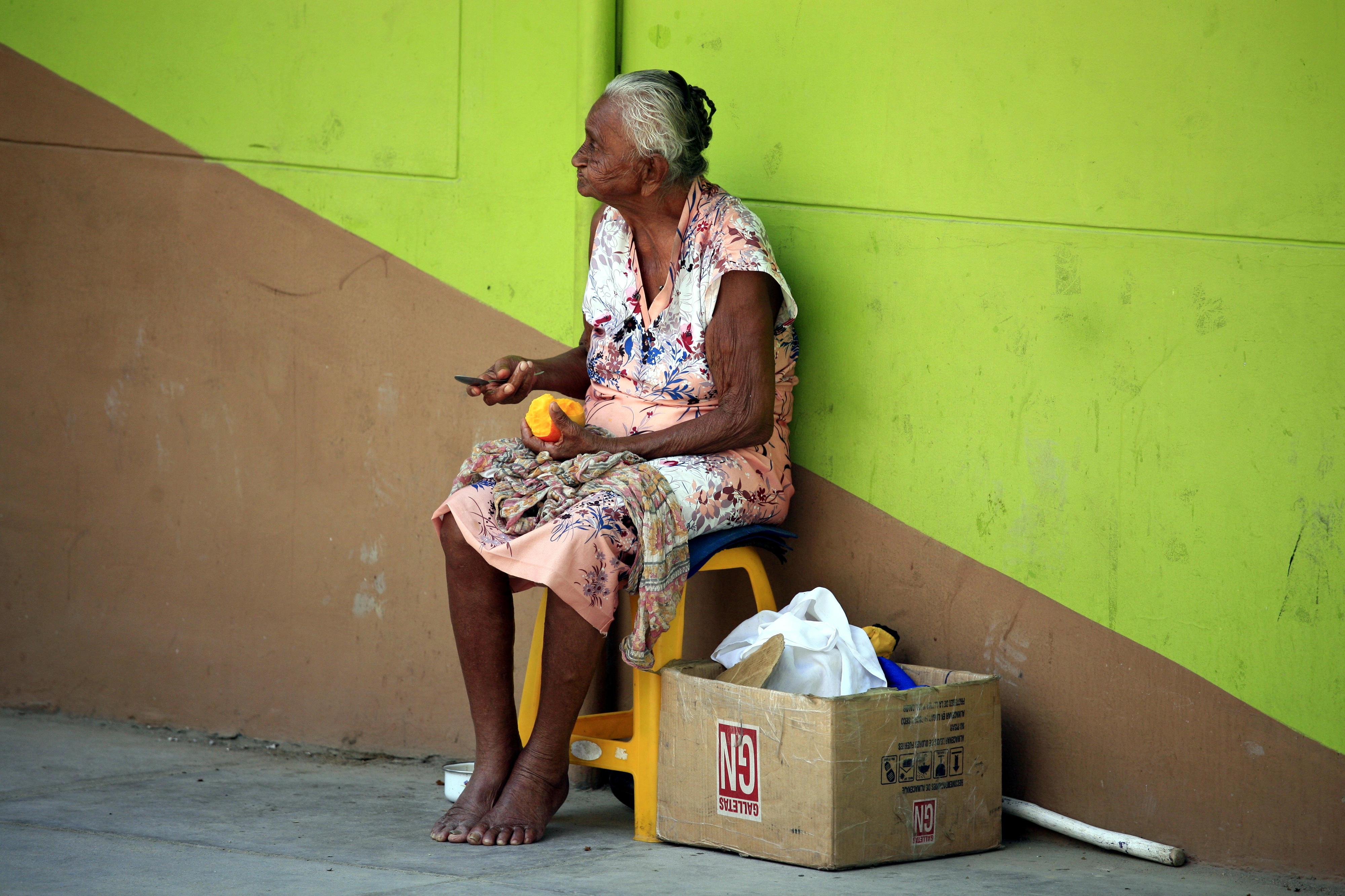 Eine ältere Frau schält eine Mango an einer Straße