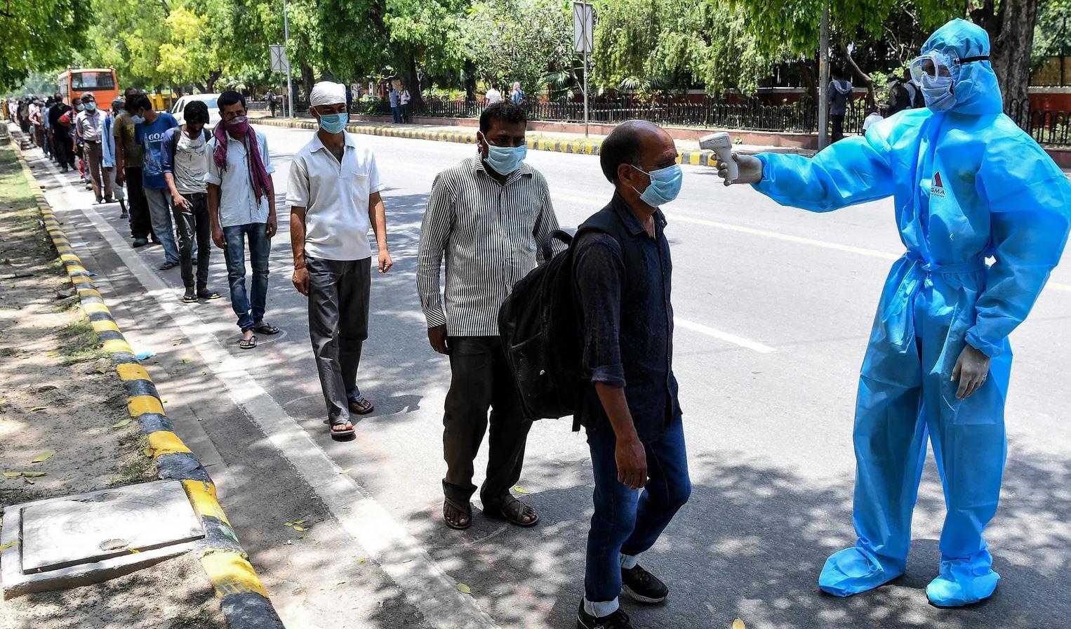 An einer Bushaltestelle in Indien wird die Körpertemperatur von Reisenden überprüft.
