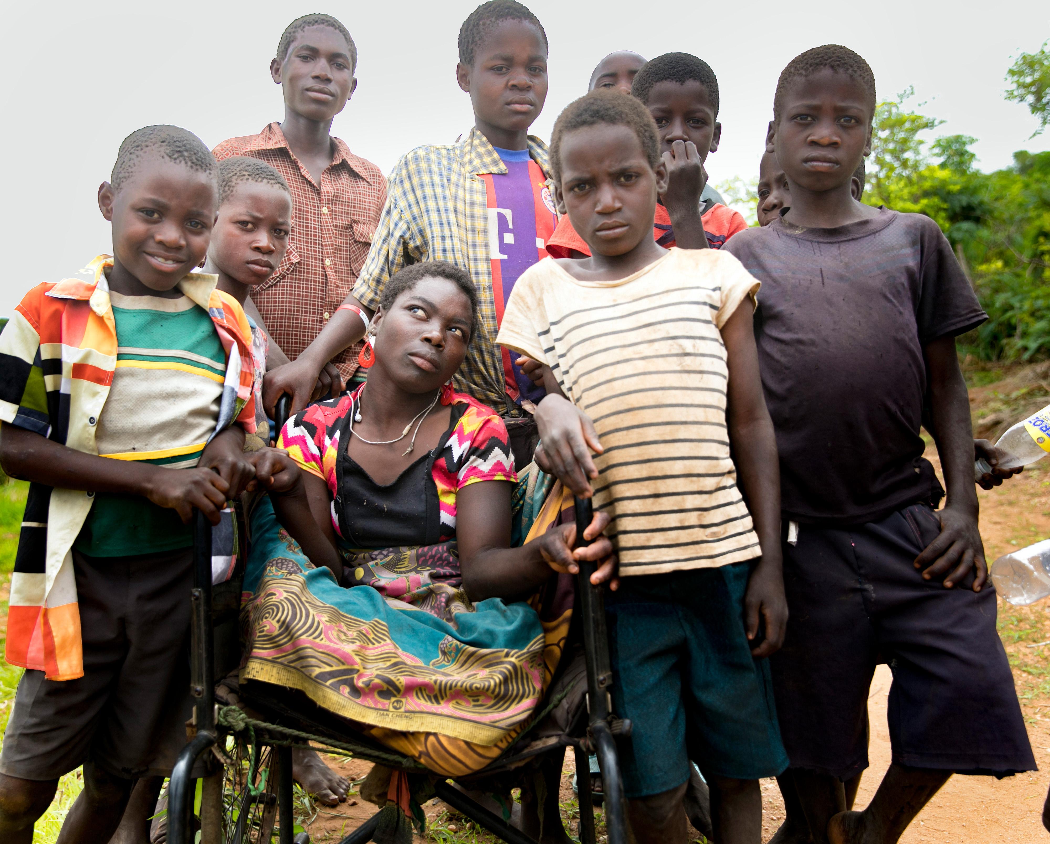 Junge Frau aus Malawi im Rollstuhl, umringt von Freunden