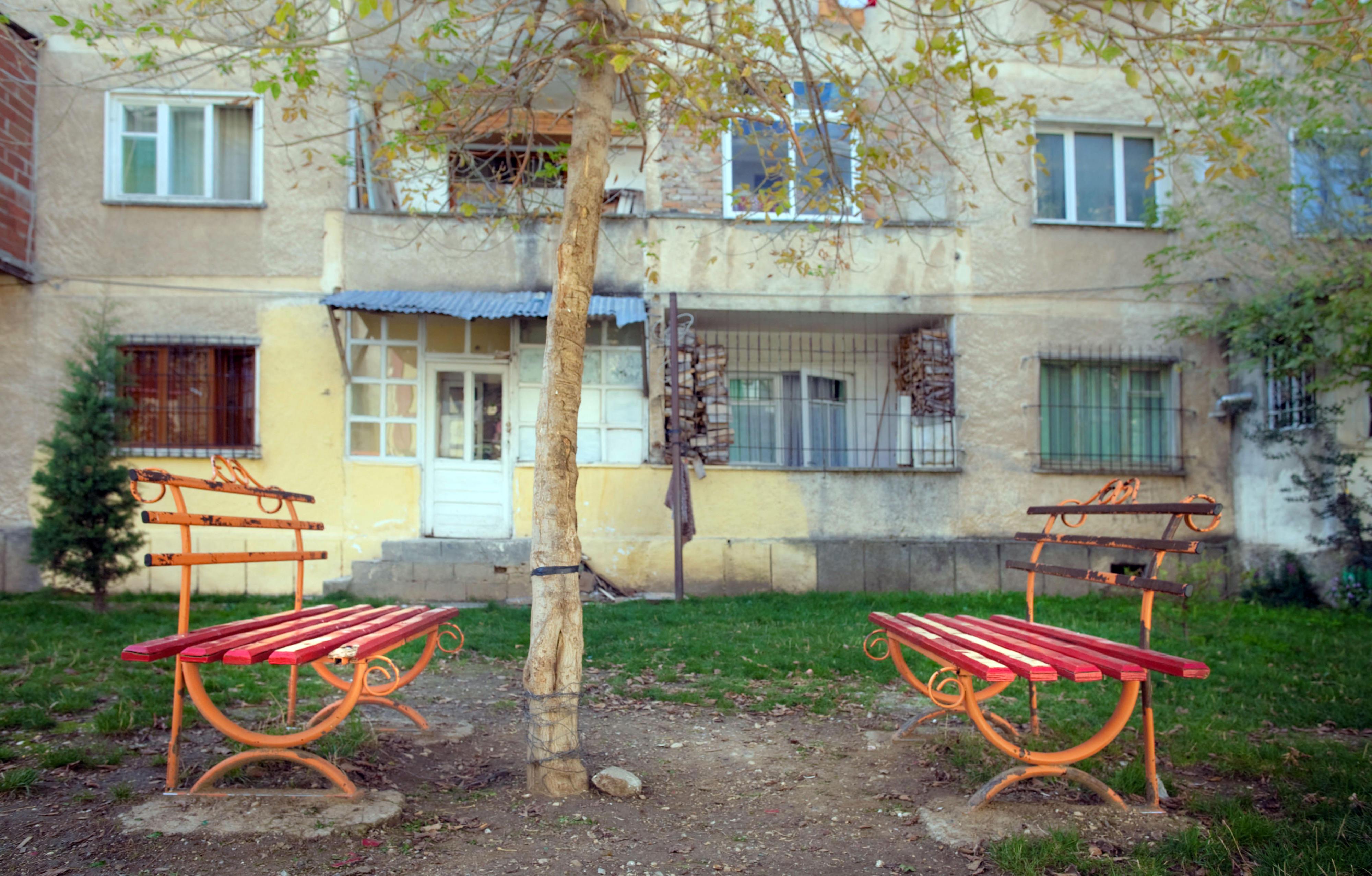 Zwei alte rote Sitzbänke im Garten eines Wohnhauses in Pogradec, Albanien