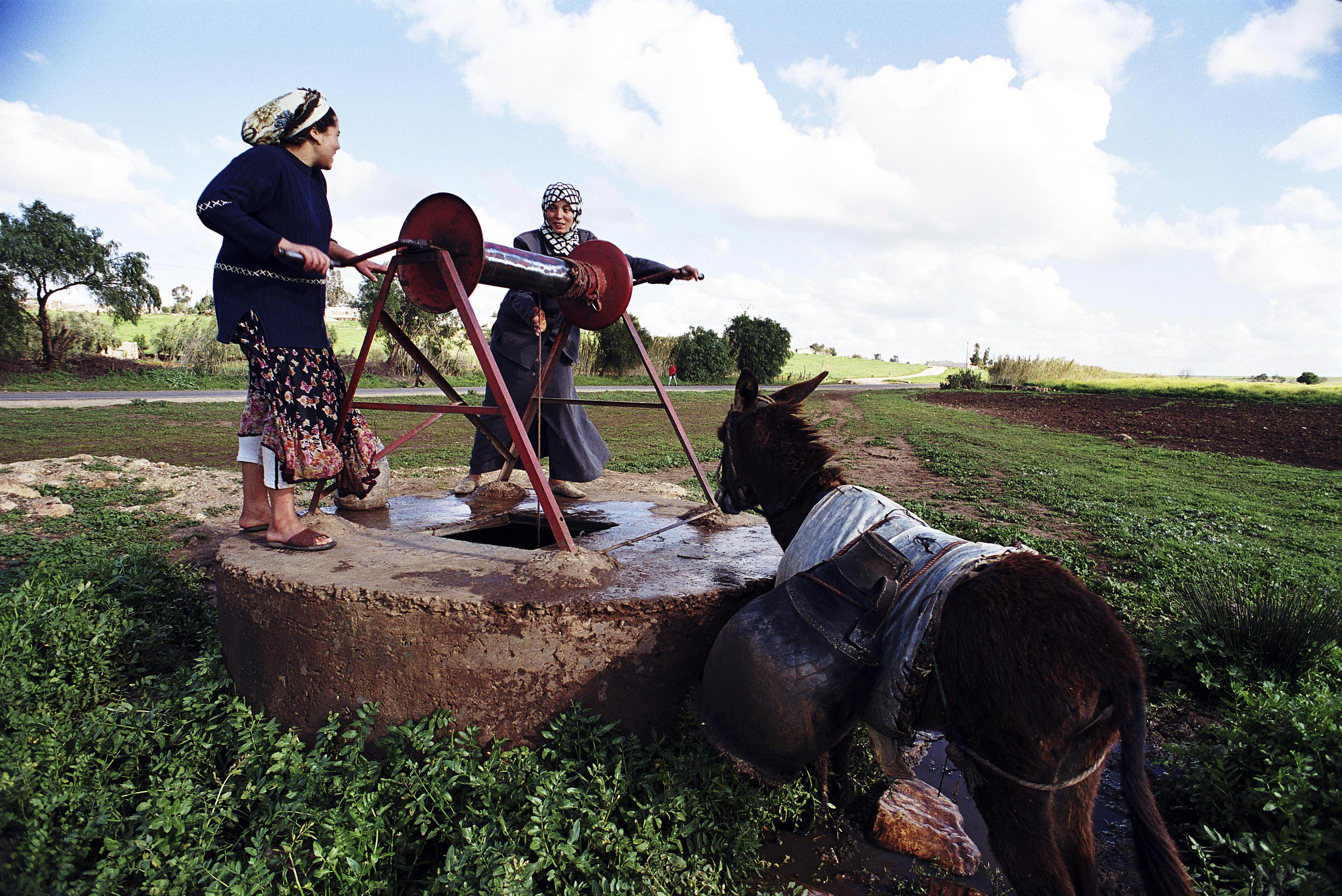 Frauen holen Wasser an einem Brunnen in Marokko.