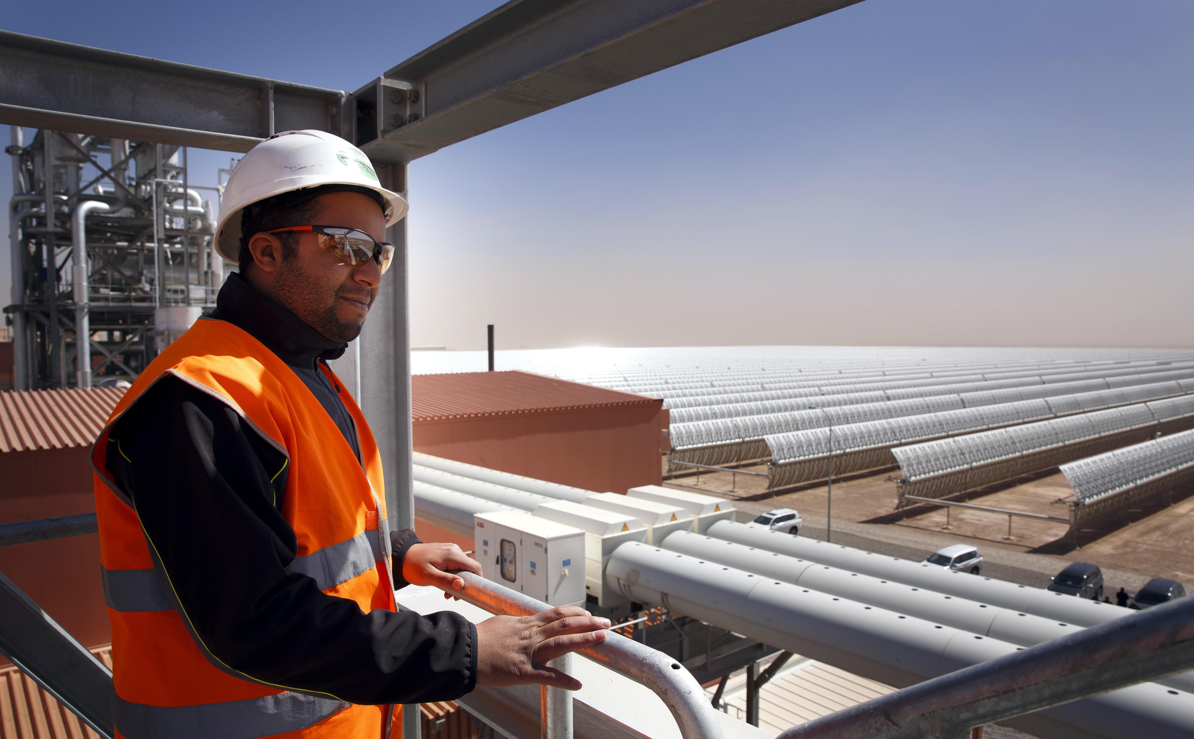 Ein Mitarbeiter des Solarkraftwerks in Ouarzazate blickt über ein Solarfeld.