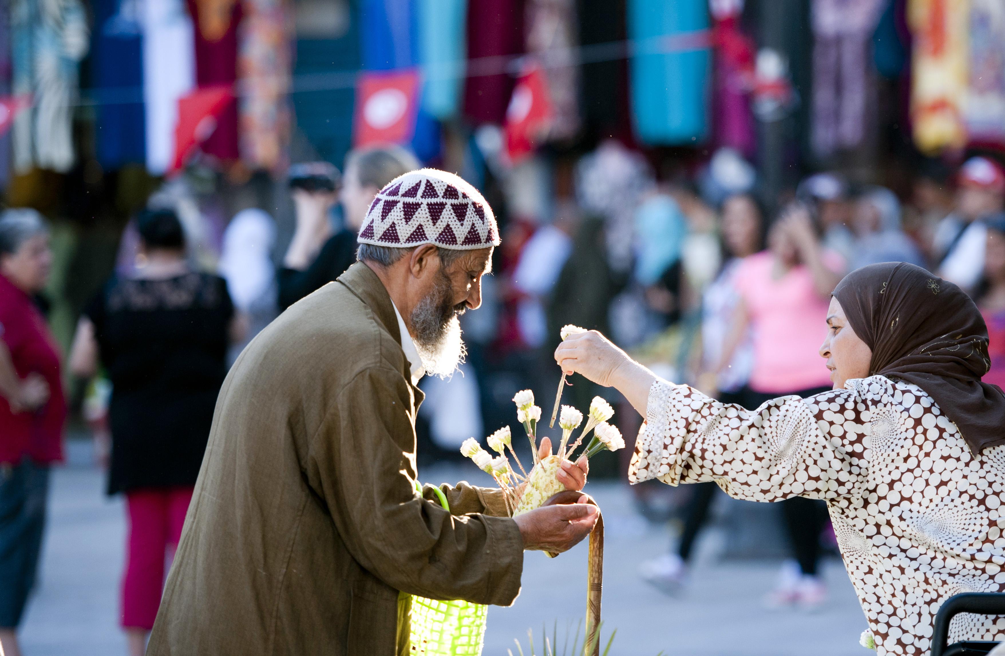 Ein Mann verkauft Blumen an eine Passantin der Altstadt von Tunis.