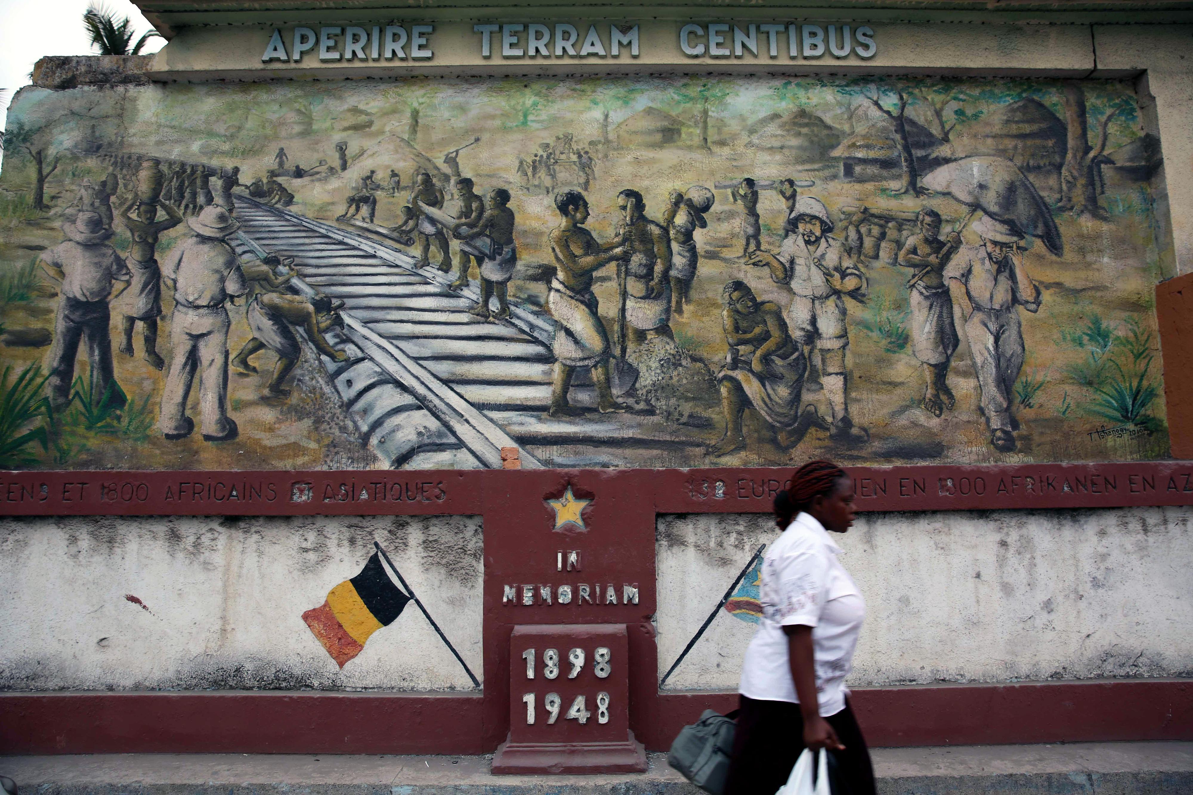 Eine Frau vor einem Wandbild am Bahnhof von Kinshasa, der Hauptstadt der DR Kongo.