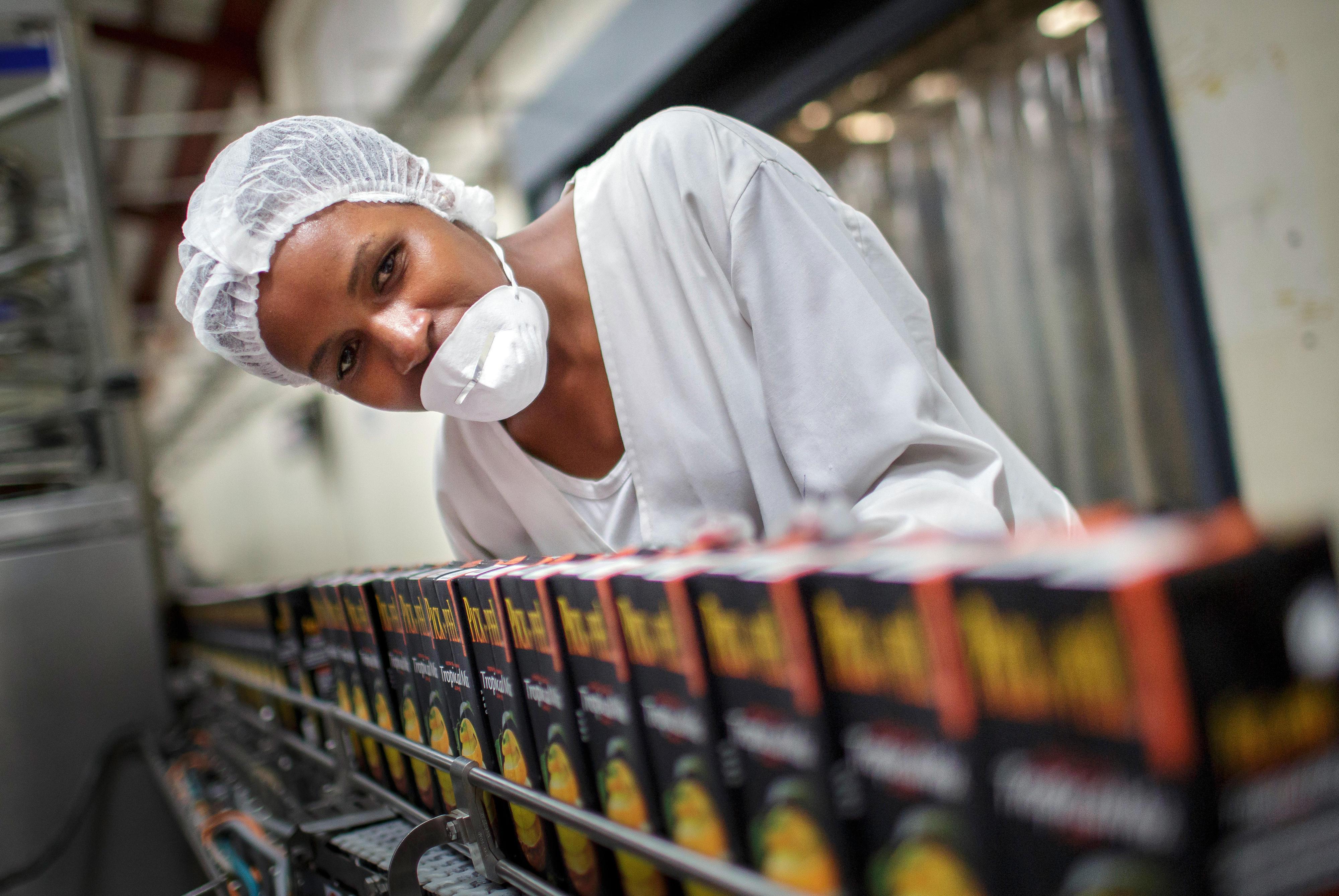 Eine Mitarbeiterin kontrolliert ein Fließband, auf dem Tetrapacks mit Fruchtsaft befördert werden.