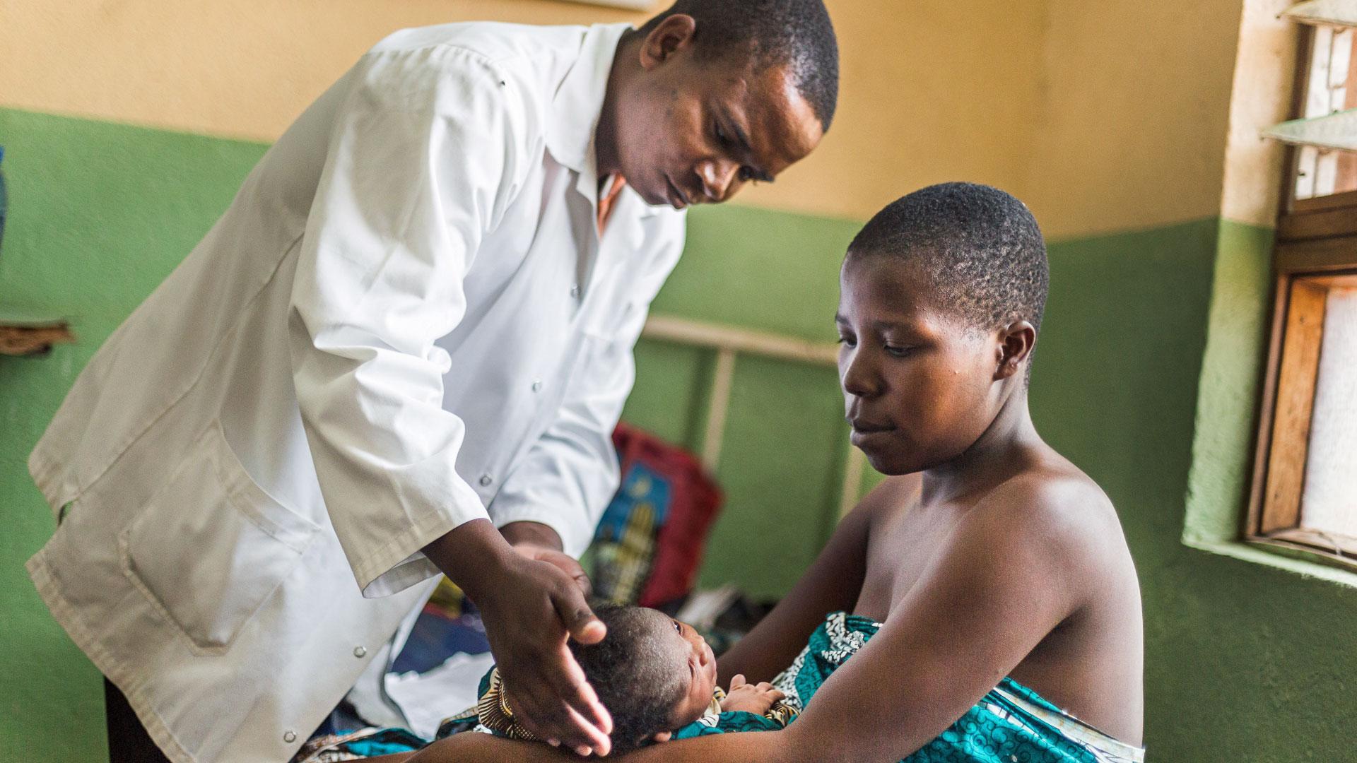 Eine Mutter ist mit ihrem Baby zum Arzt gekommen, der das Kind nun untersucht.