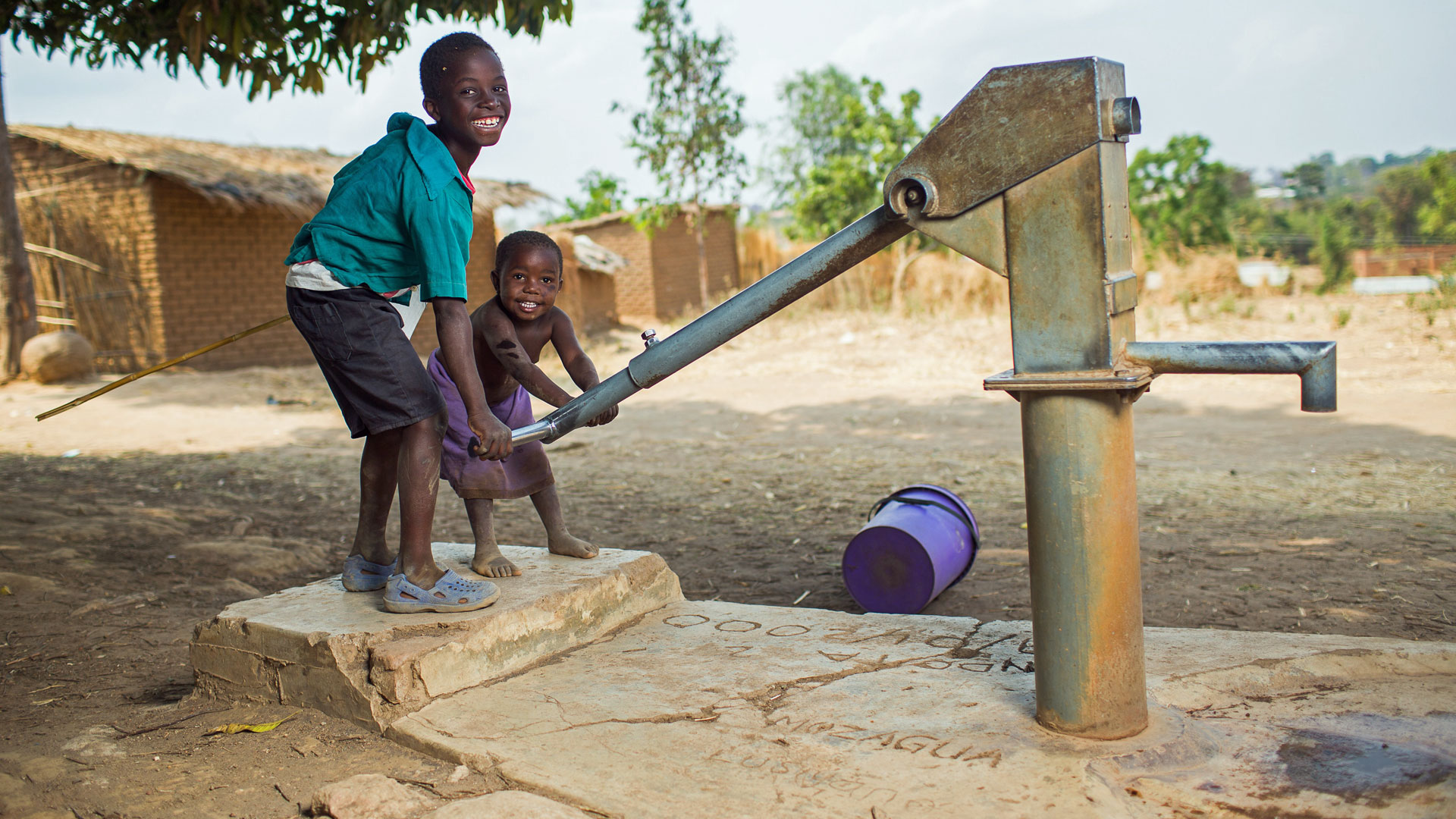 In einem Dorf nahe Bilira (Malawi) spielen zwei Kinder mit der Wasserpumpe eines Brunnens.