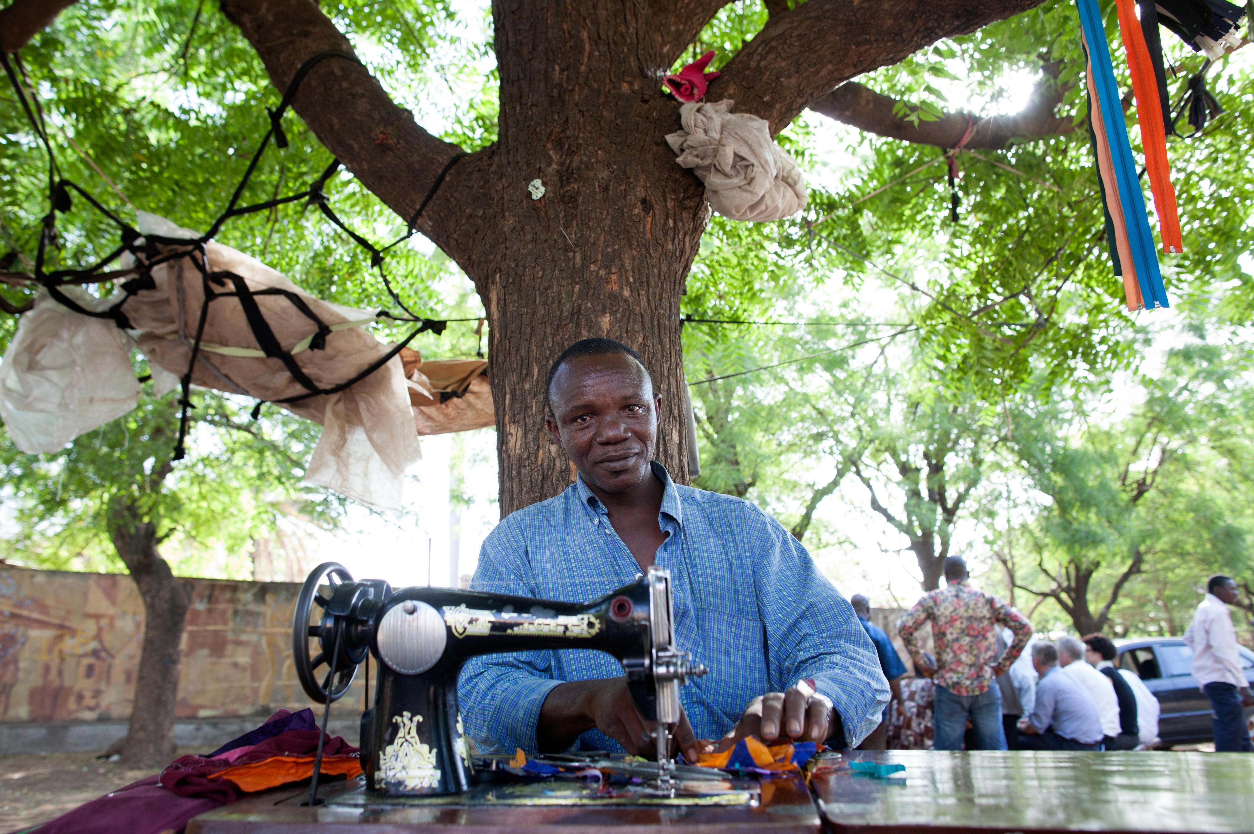 Schneider an einer Nähmaschine auf einer Straße in Bamako, Mali