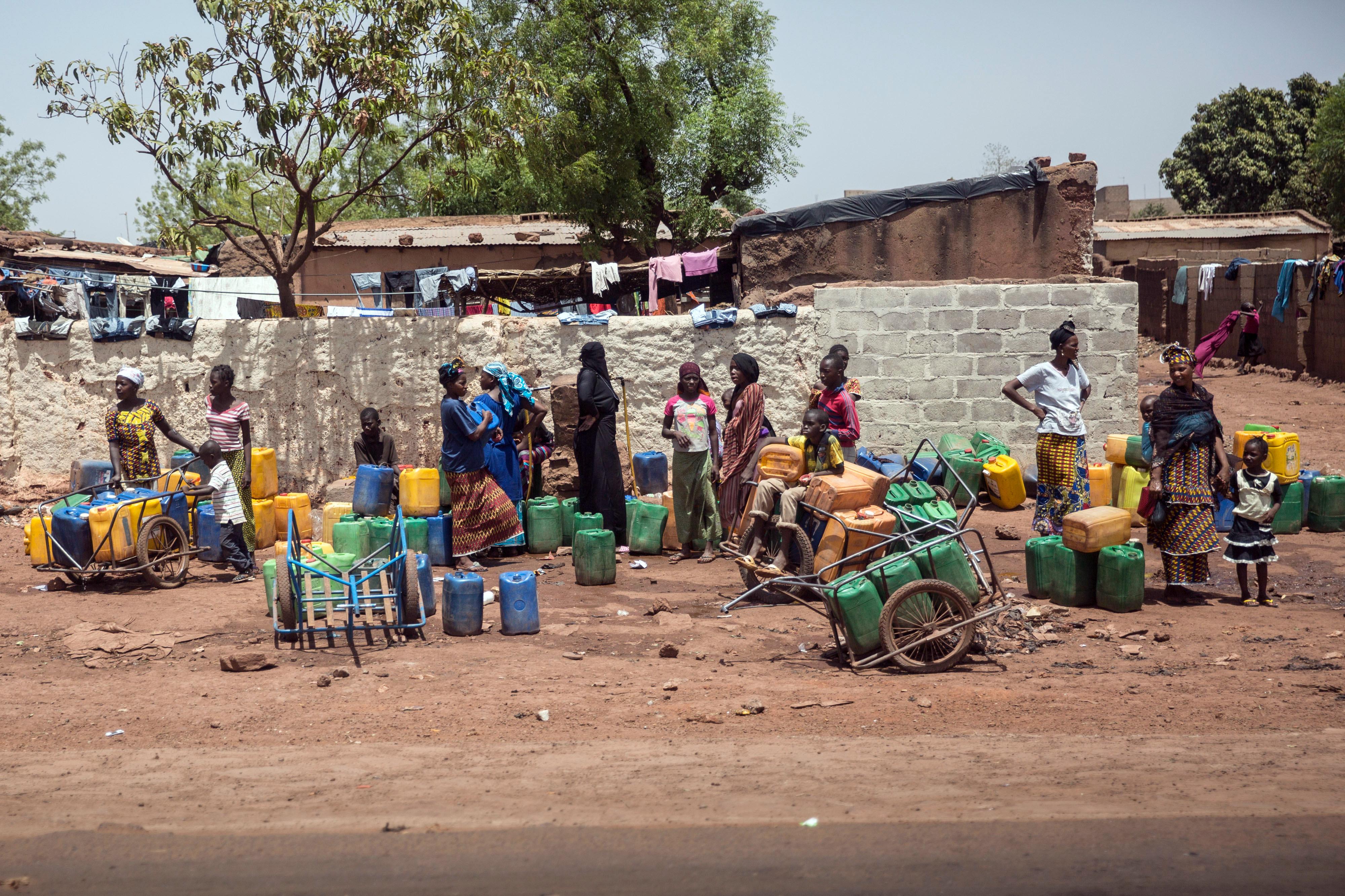 Frauen stehen mit Wasserkanistern an einer Straße in Bamako.