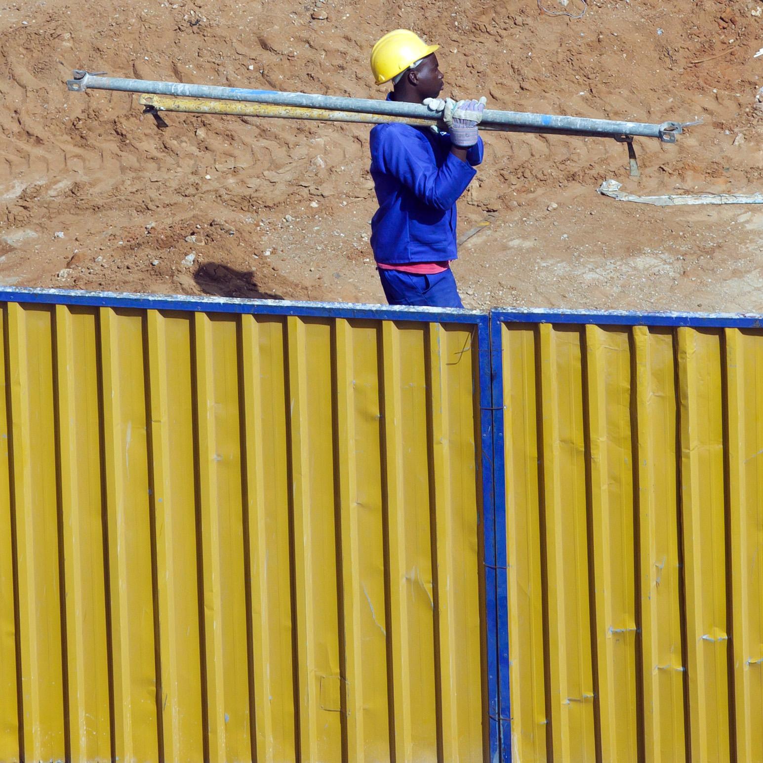 Ein Bauarbeiter trägt Stahlrohre über eine Baustelle in Mosambiks Hauptstadt Maputo.