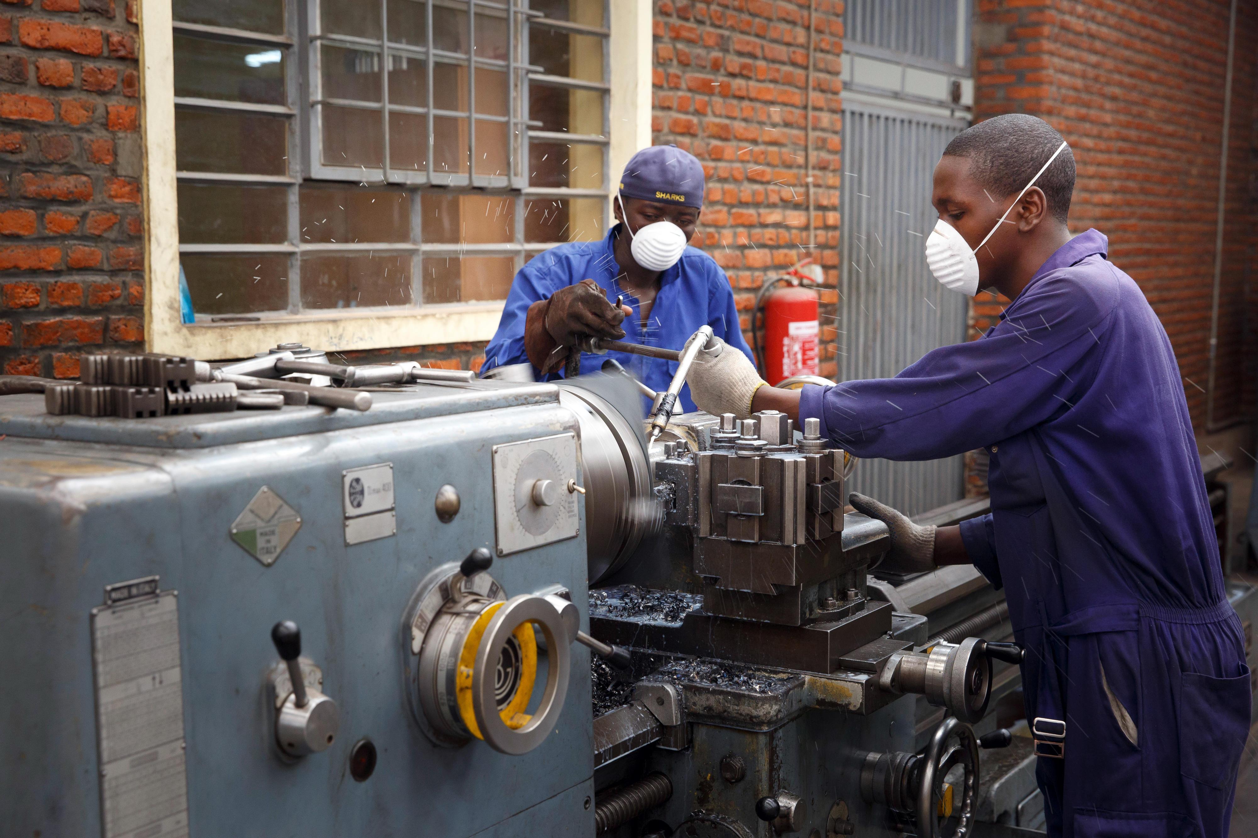 Zwei Auszubildende im Bereich Metallbau am Integrated Polytechnical Regional College (IPRC) in Kigali, Ruanda, bedienen eine Maschine.