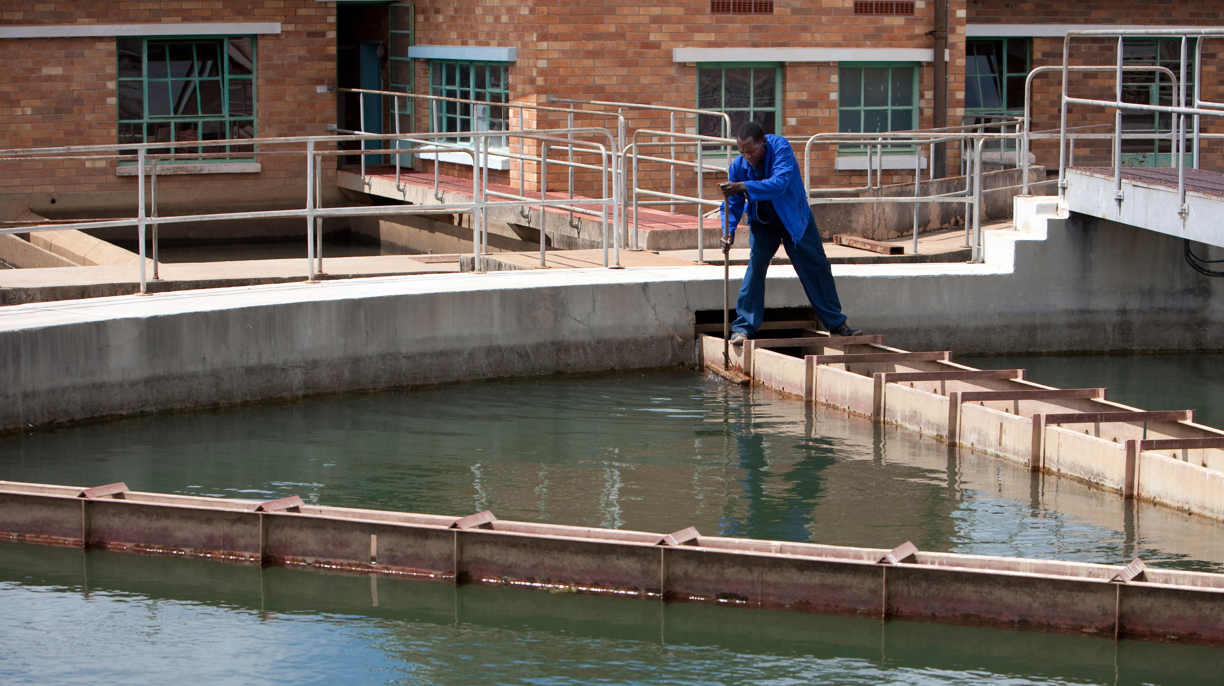 Mitarbeiter bei der Reinigung eines Filterbeckens eines Wasserwerkes in Livingstone, Sambia