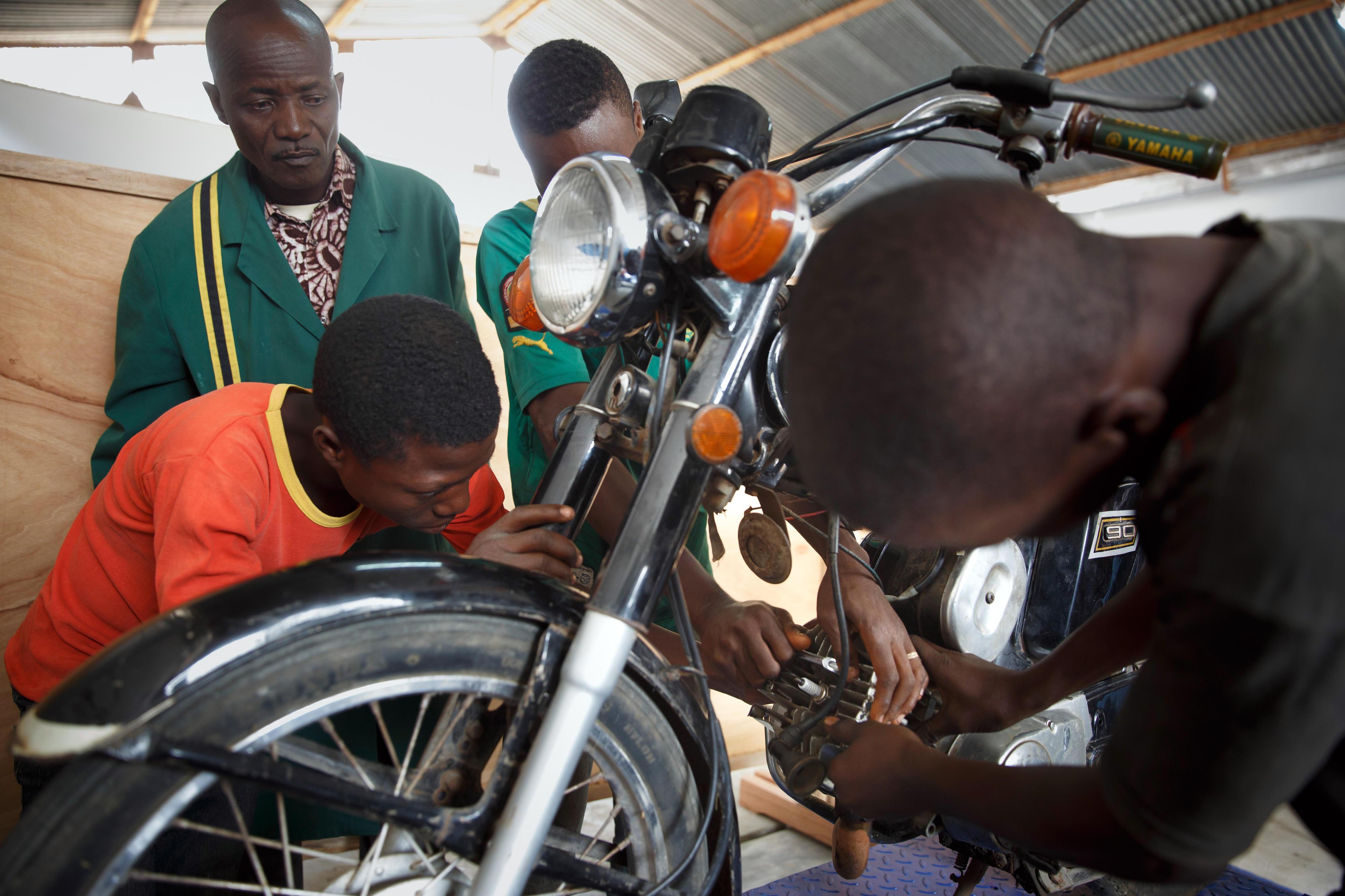 Schüler des Ausbildungsganges Kfz-Mechanik der Berufsschule in Sokodé (Togo) reparieren ein Motorrad.