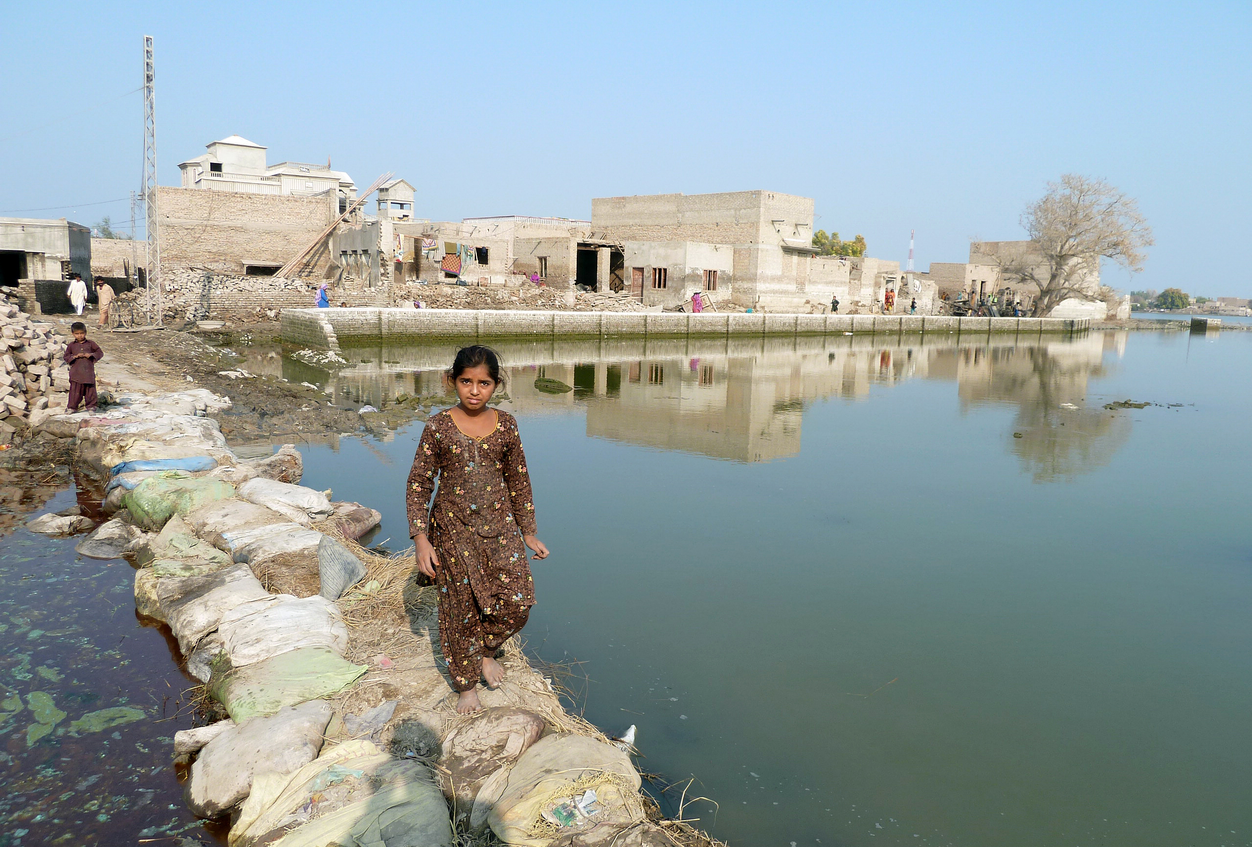 Ein junges Mädchen auf einer Behelfsbrücke nach einer Überflutung in der Provinz Sindh in Pakistan