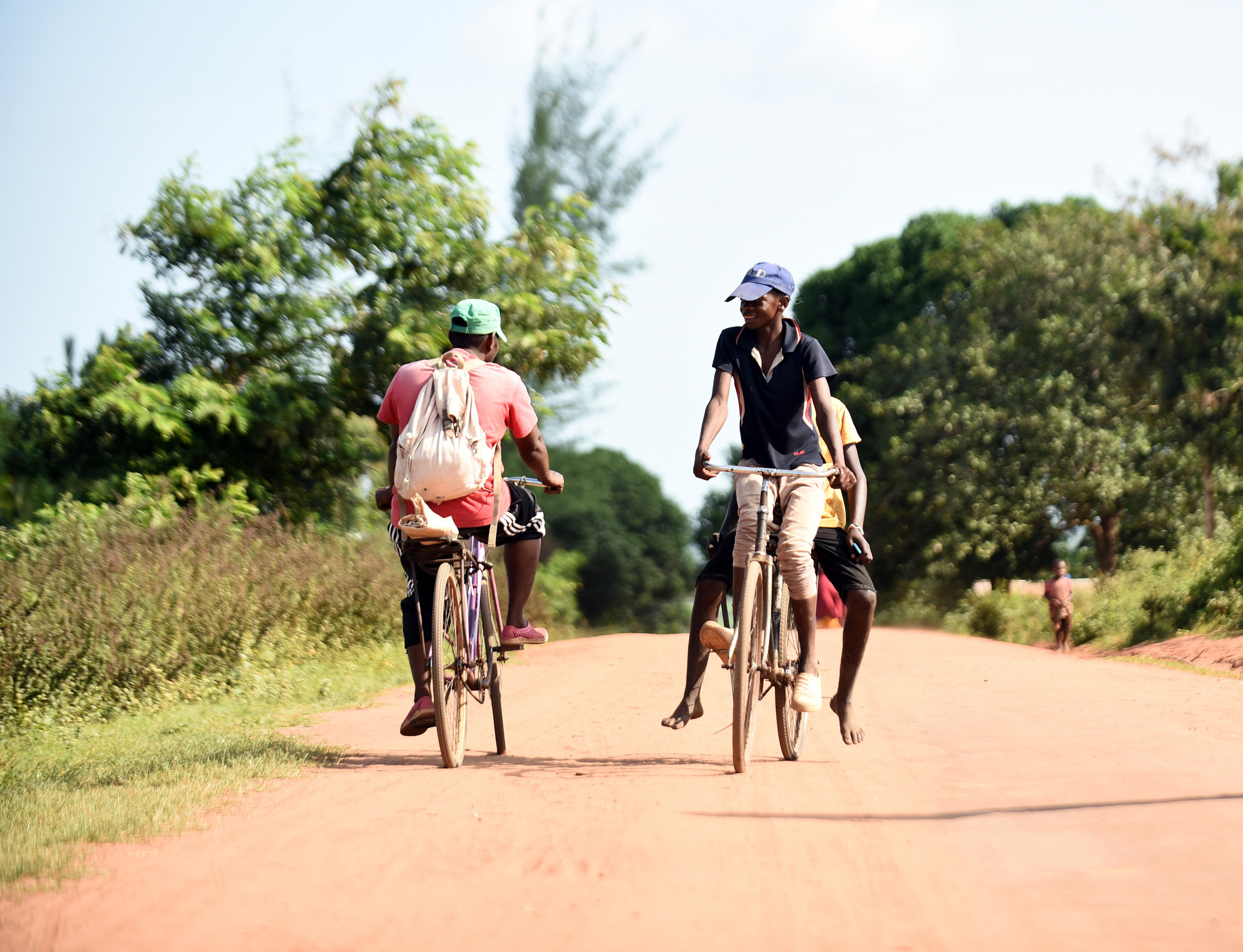 Teenagers on bicycles on a Kenyan country road