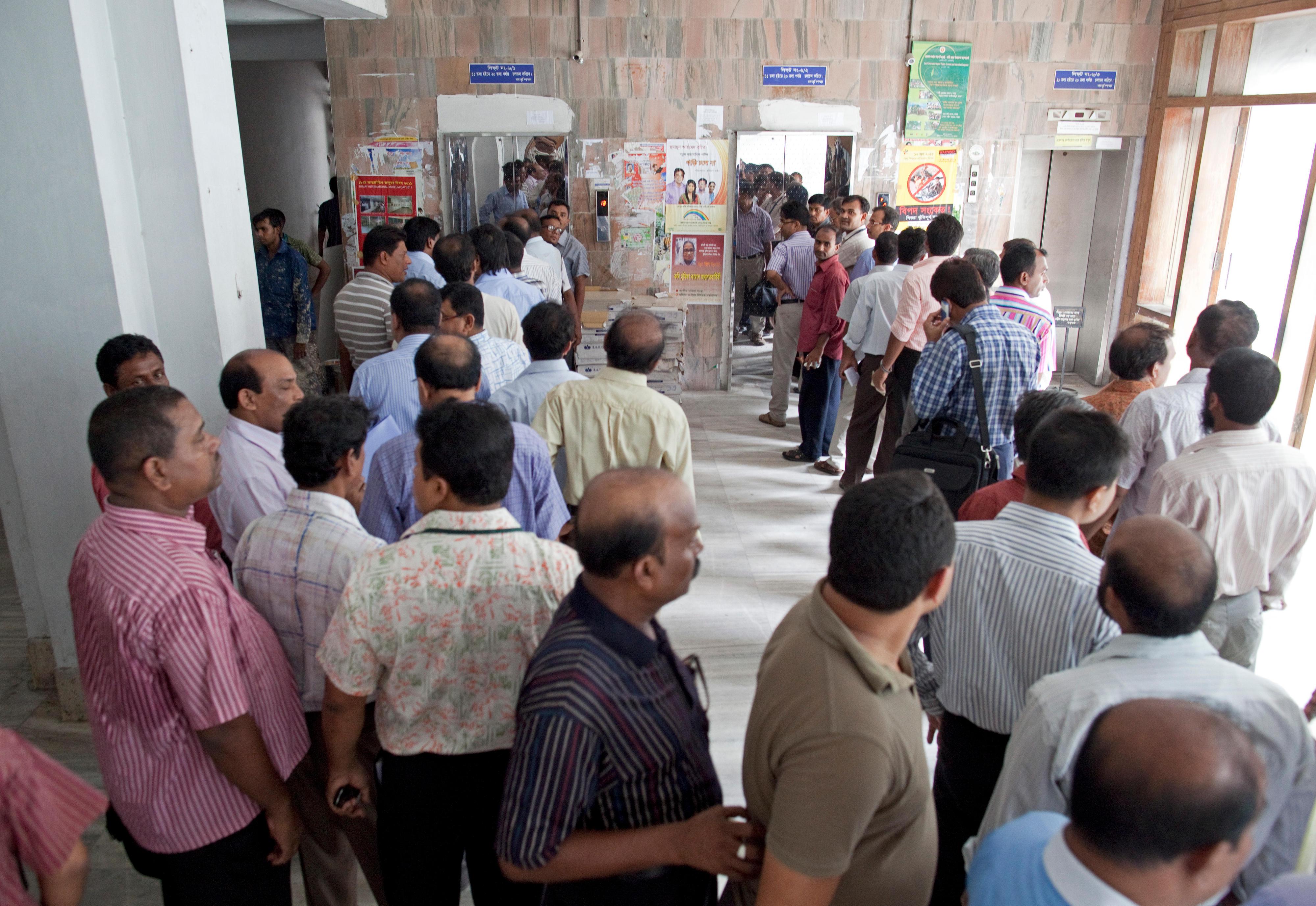 Mitarbeiter im Finanzministerium in Dhaka, Bangladesch, warten vor ihrem Arbeitsbeginn auf Aufzüge.
