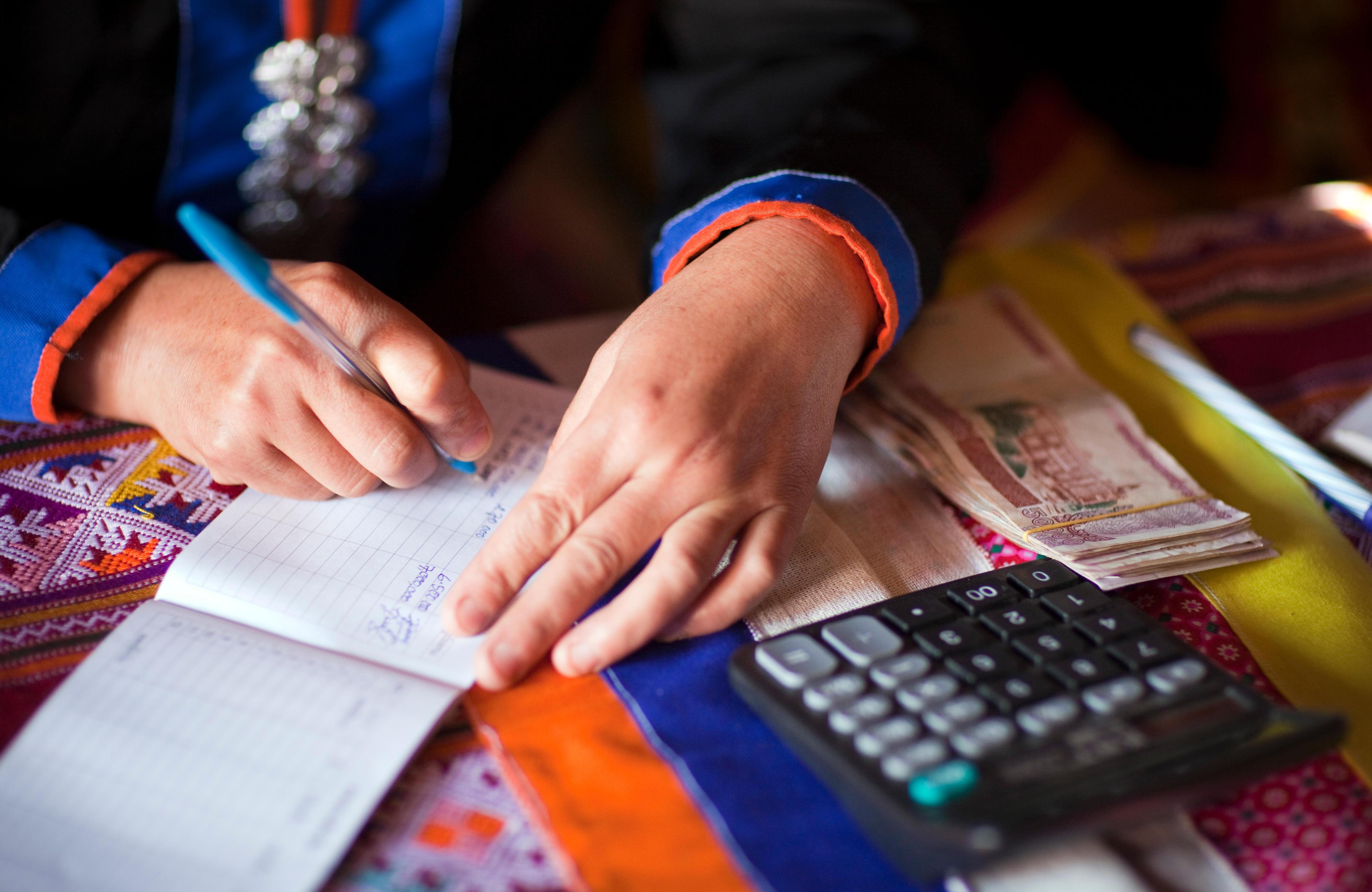 Am monatlichen Banktag zahlen Mikrofinanzkunden Geld beim Dorfbankenkomitee der Dorfbank in Pung, Laos, ein.