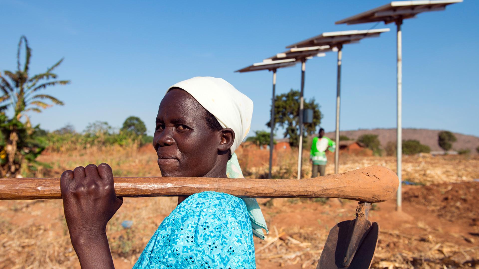 Eine Bäuerin in Malawi vor einer Solaranlage, die den Strom für die Pumpe eines Tröpfchenbewässerungssystems liefert