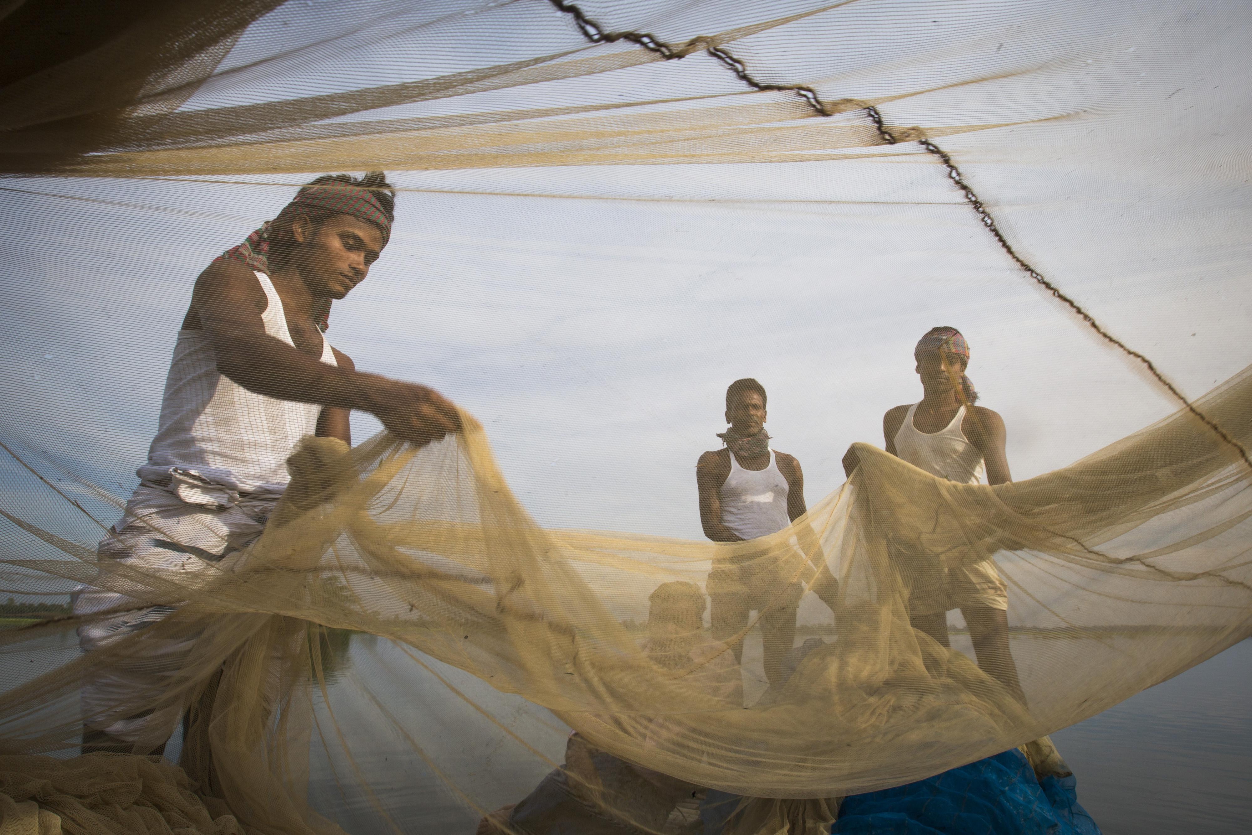 Drei Fischer mit Fischernetz in Bangladesch