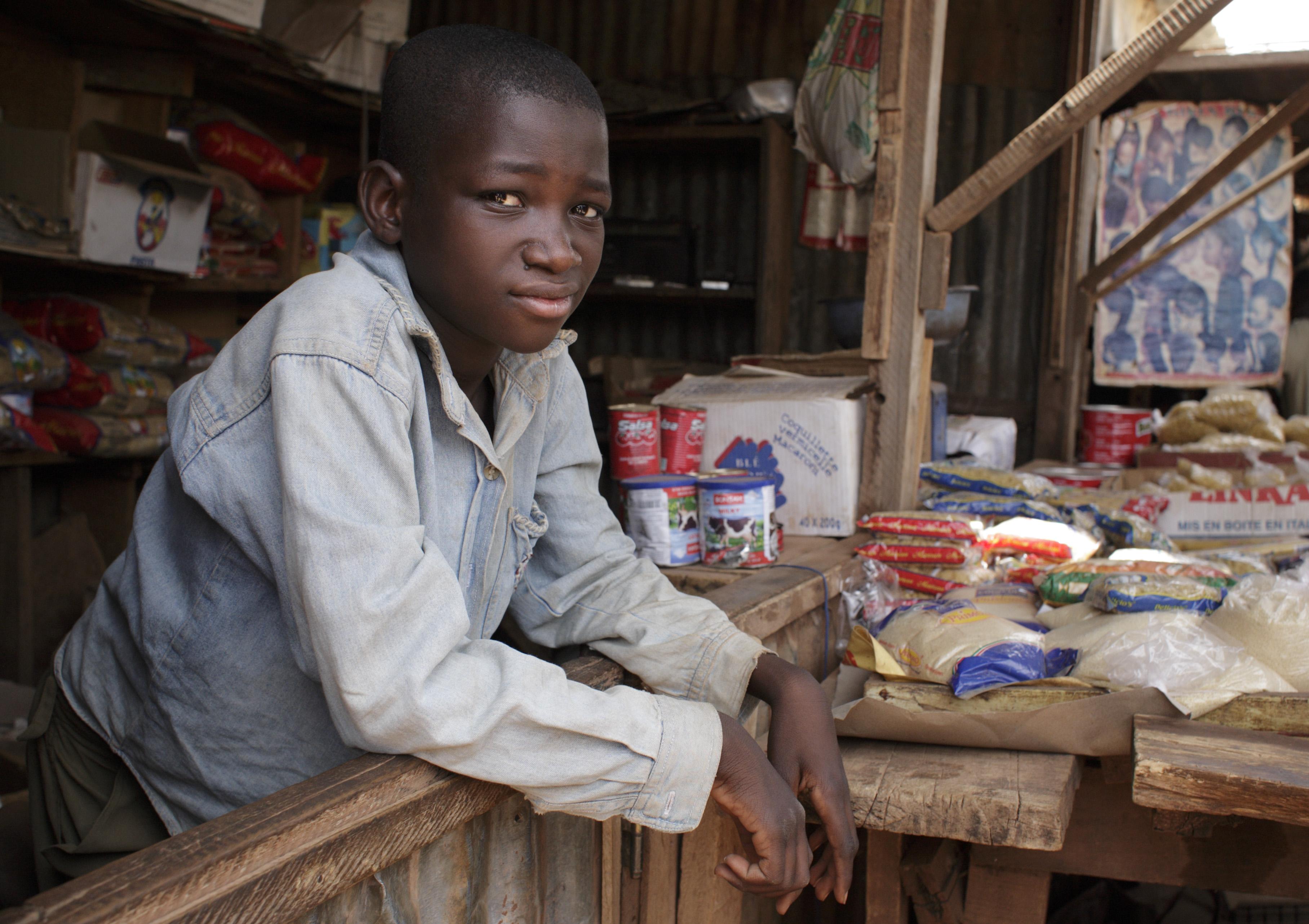 Ein Jugendlicher arbeitet in Burkina Faso an einem Marktstand.