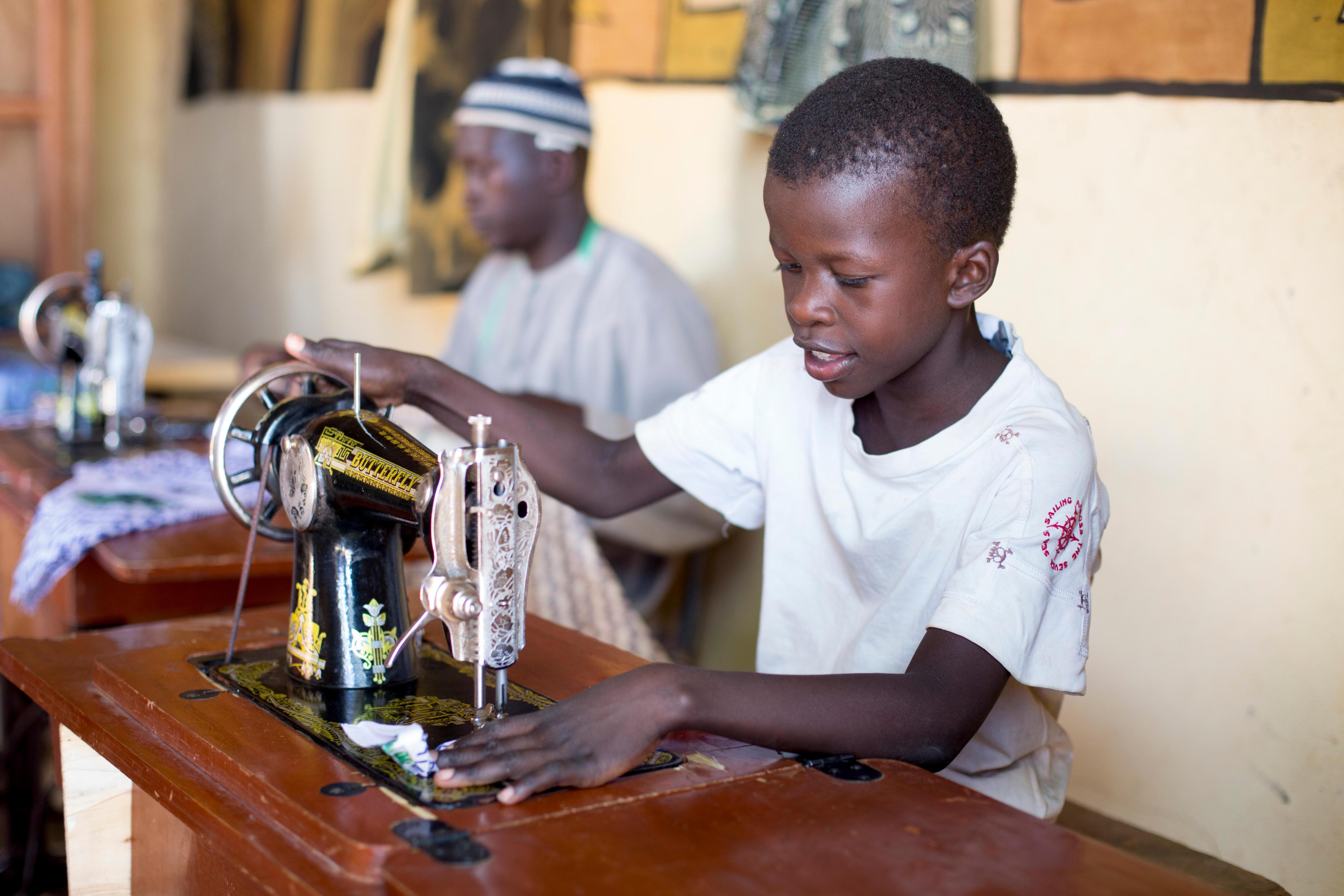 Ein Junge in Mali arbeitet an einer Nähmaschine.