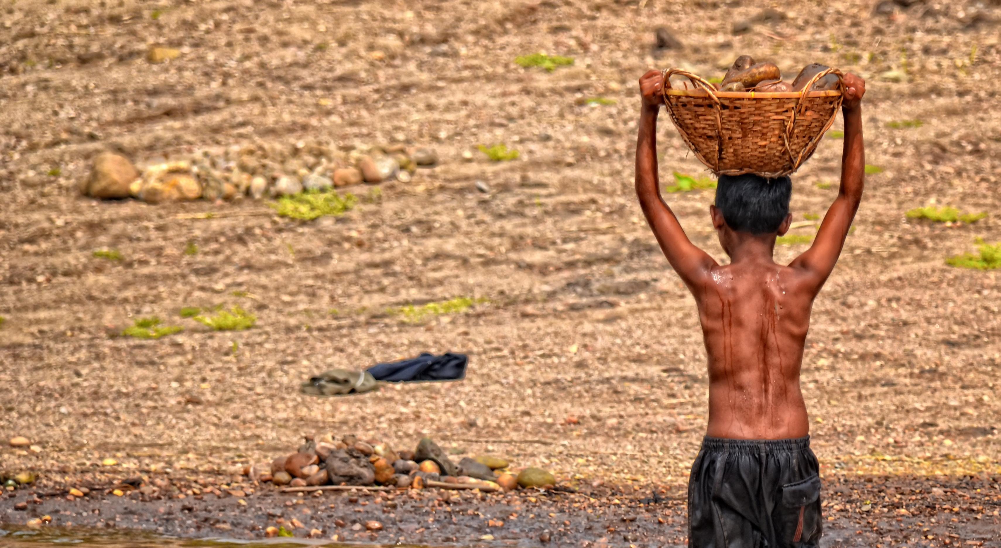 Ein Junge in Bangladesch transportiert einen mit Steinen gefüllten Korb.