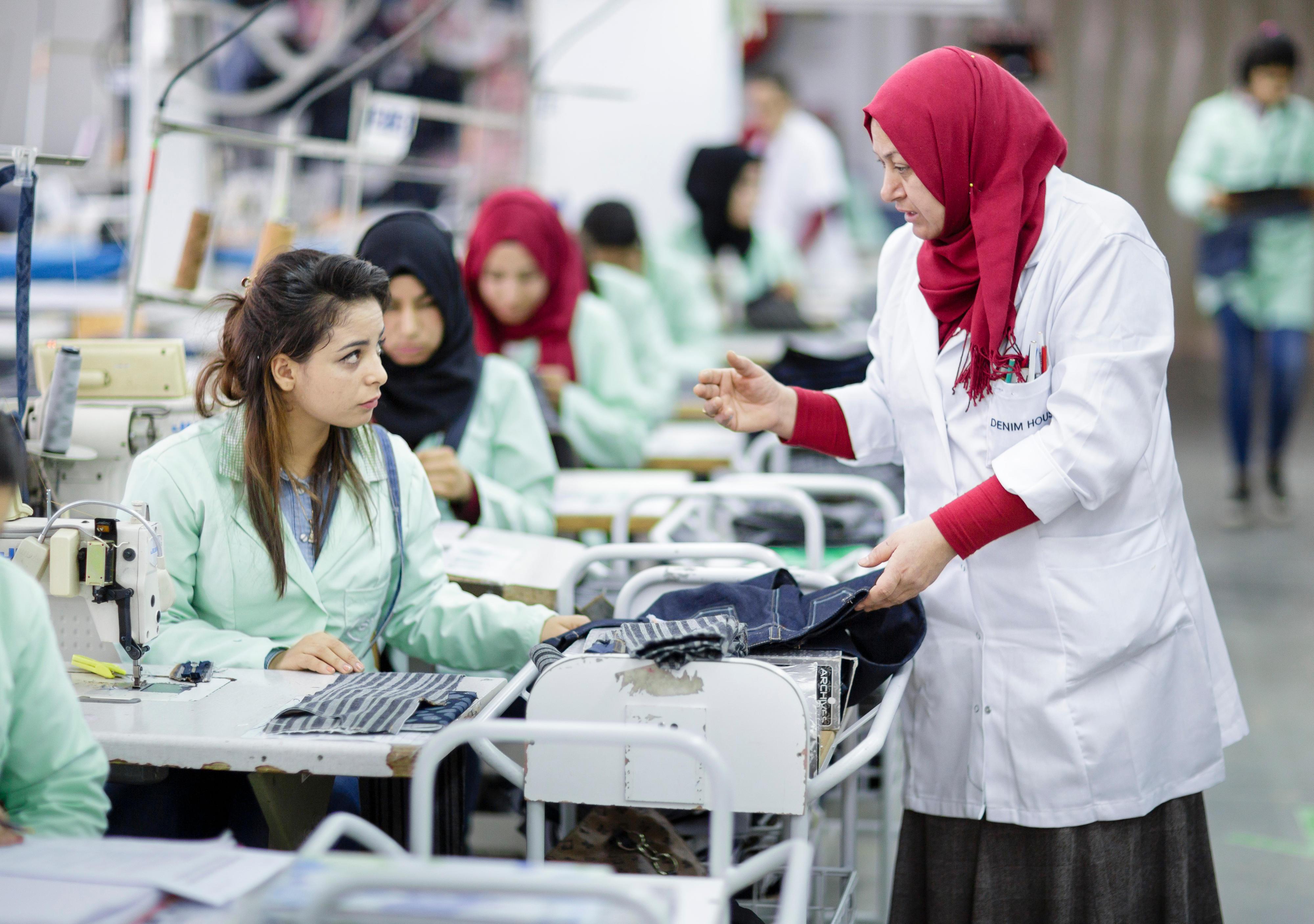 Ausbildungswerkstatt eines Textilunternehmens in Tunesien. Eine Ausbilderin leitet eine junge Näherin an.