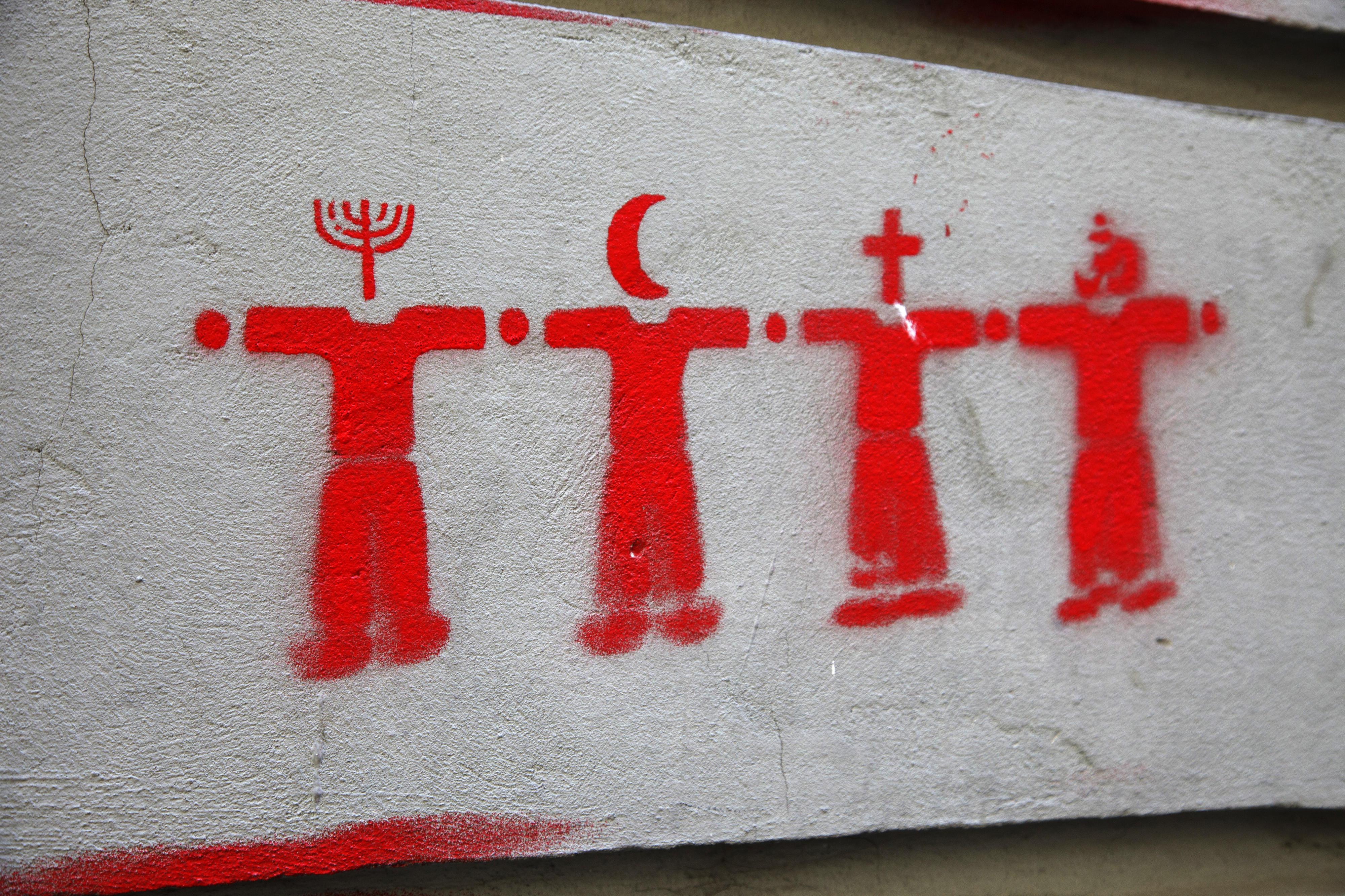 Symbolbild Weltreligionen, dargestellt in Form eines Graffitis auf einer Zementoberfläche: Vier rote Figuren symbolisieren verschiedene Religionen