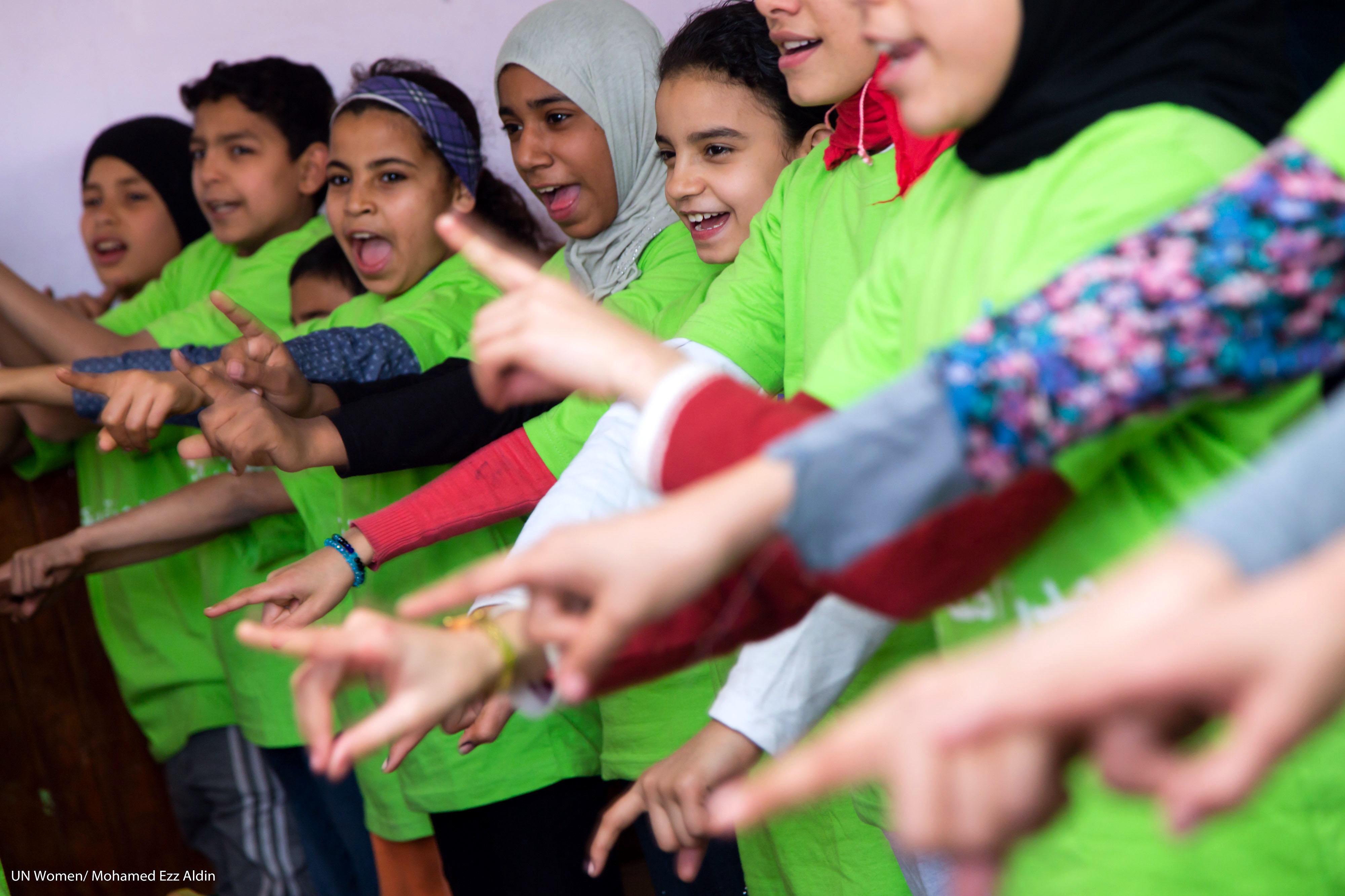 Kinder in Ägypten singen während einer Sensibilisierungskampagne zur Beendigung von Gewalt gegen Frauen. Die Kinder stehen in einer Reihe und halten ihre ausgestreckten Zeigefinger nach vorn.