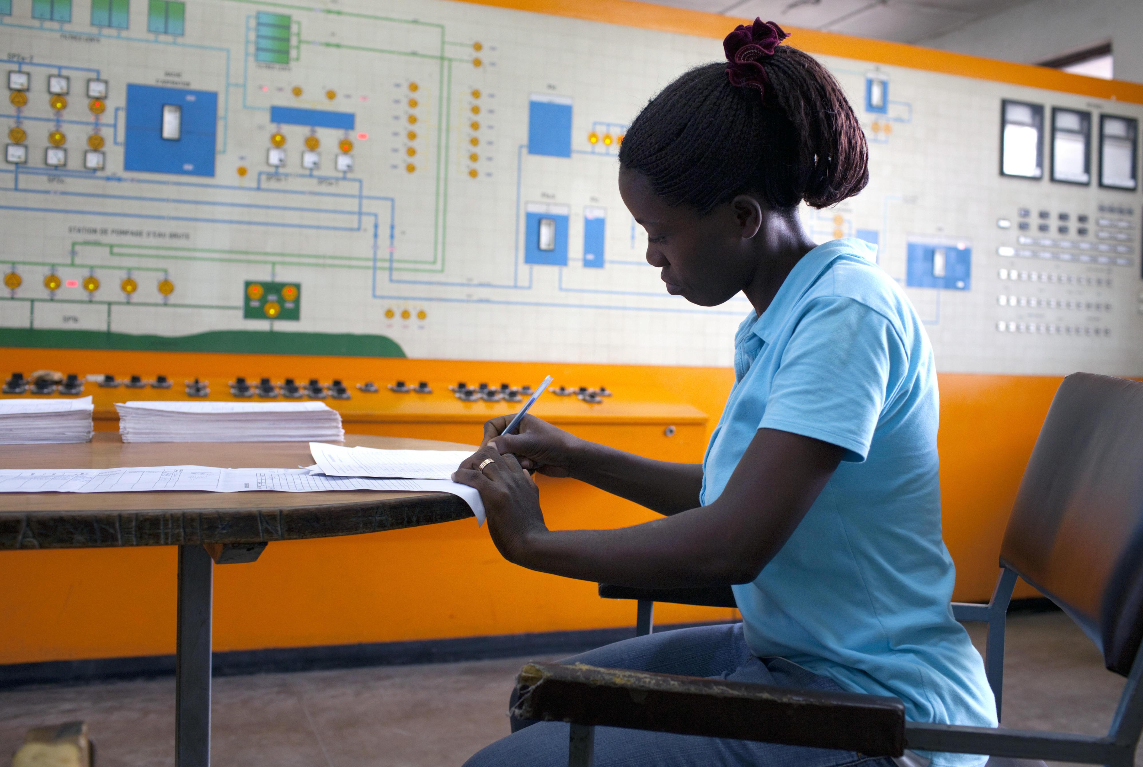 Eine technische Angestellte in der Schaltzentrale der Pumpstation eines Wasserprojekts der KfW Entwicklungsbank in Bujumbura in Burundi sitzt an einem Tisch und schreibt mit einem Kugelschreiber in ein Formular.