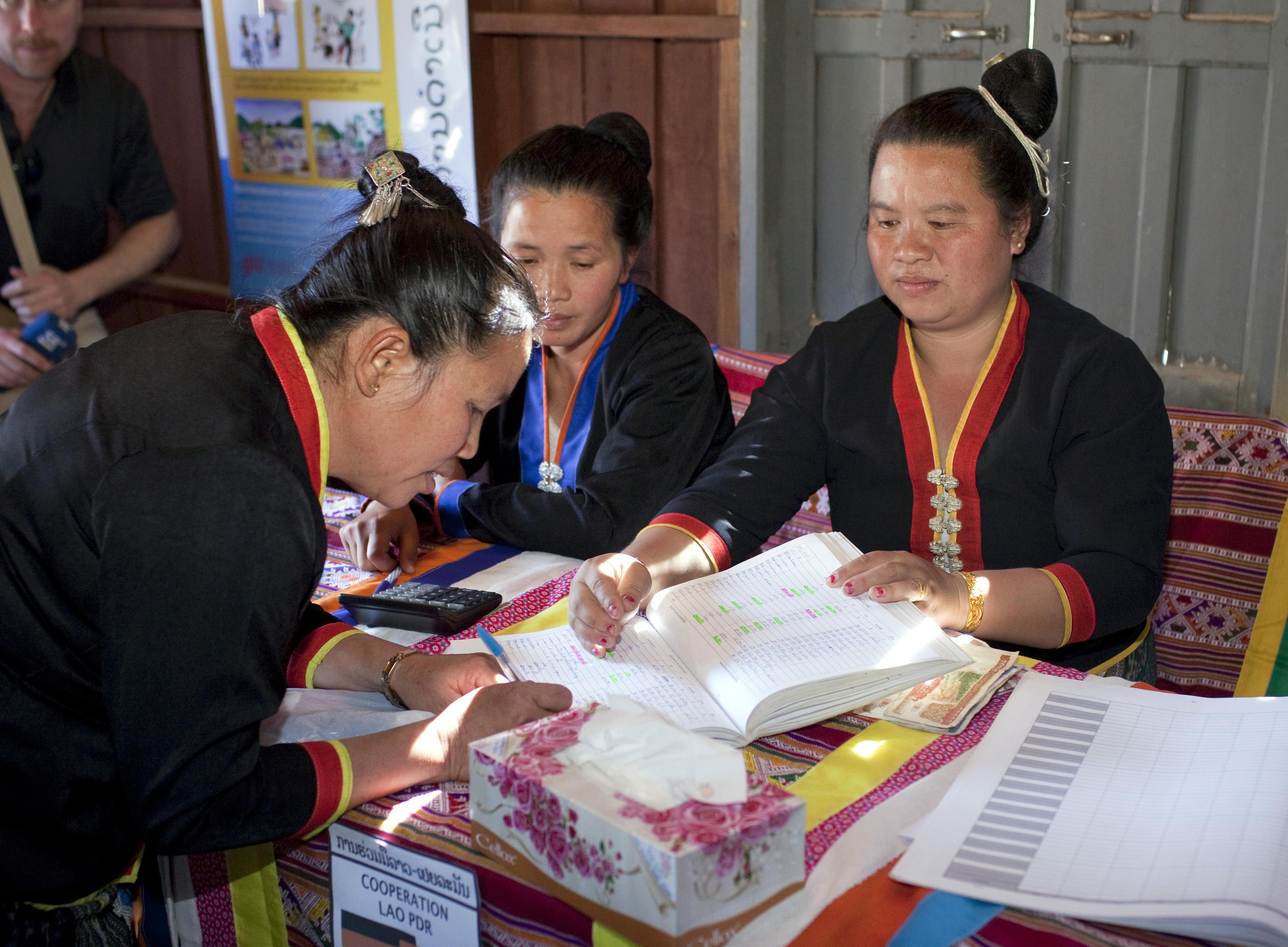 Laos: Am monatlichen Banktag zahlen Mikrofinanzkundinnen Geld beim Dorfbankenkomitee der Dorfbank in Pung ein. Zwei Frauen in traditioneller Kleidung sitzen hinter einem Tisch, eine weiterer steht davor und unterschreibt in einem Buch.