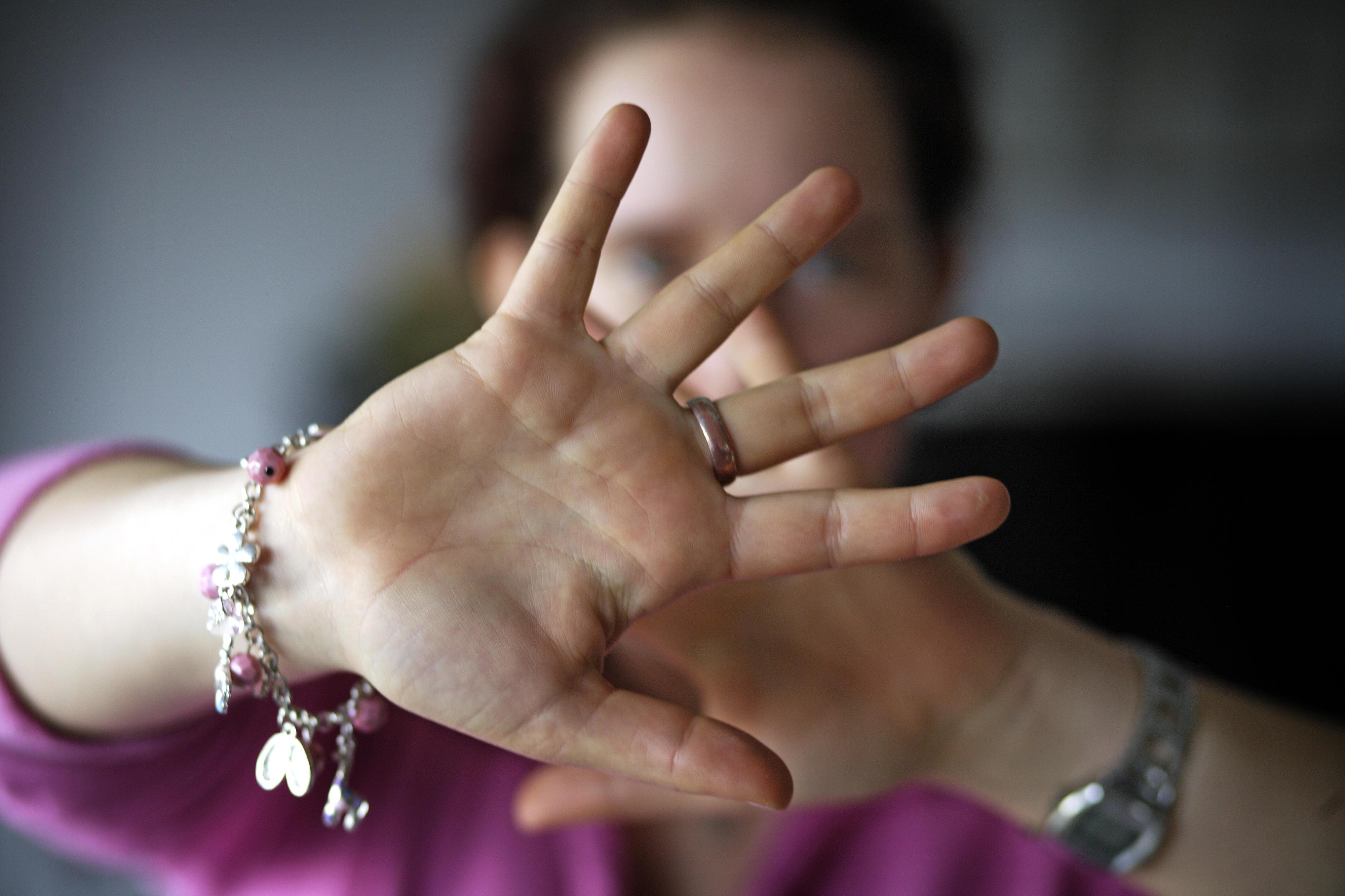 Symbolfoto: Eine Frau hält abwehrend ihre Hände vor ihren Kopf um sich zu schützen
