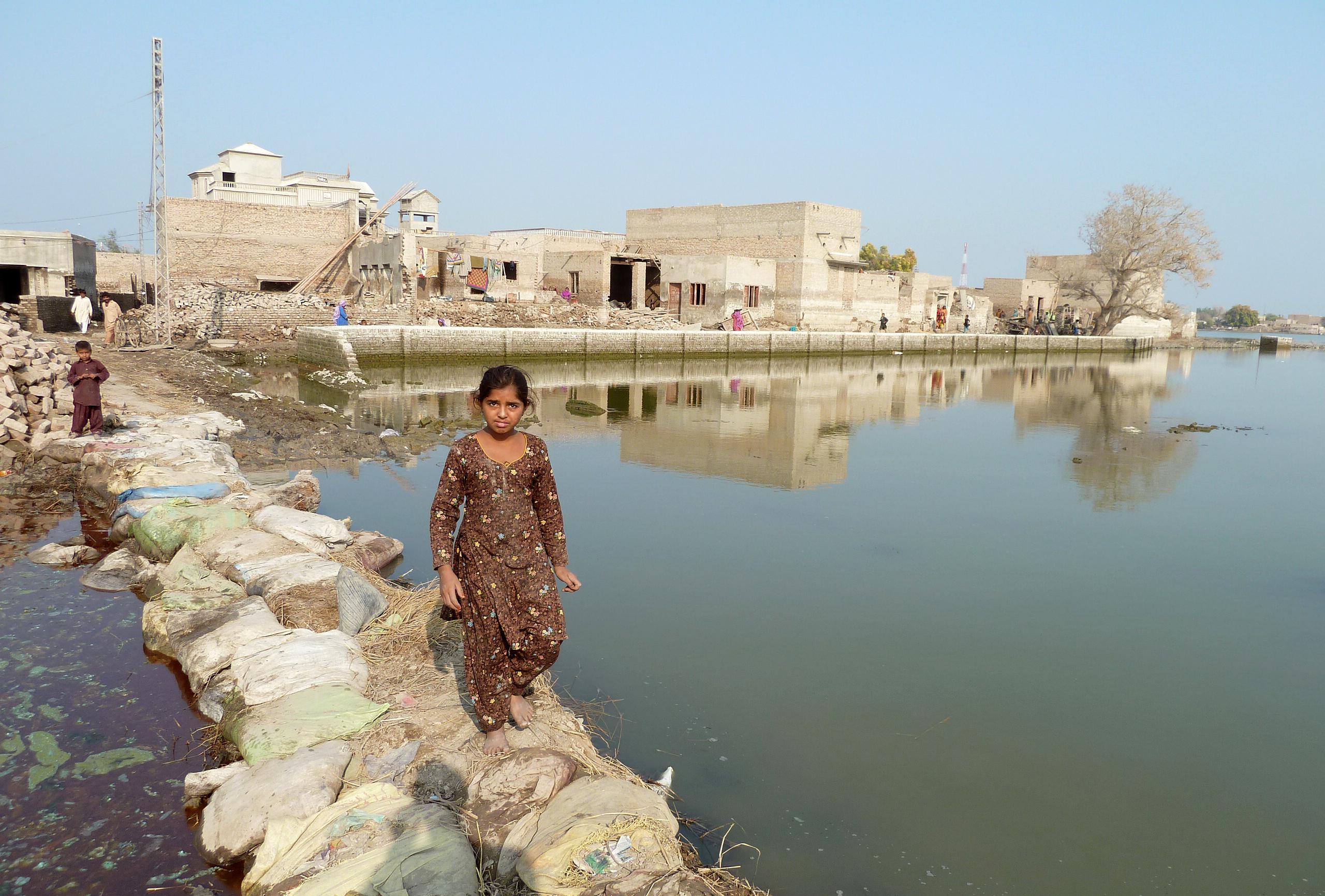 Ein junges Mädchen steht auf einer Behelfsbrücke aus Sandsäcken, nach einer Überflutung in der Provinz Sindh in Pakistan.