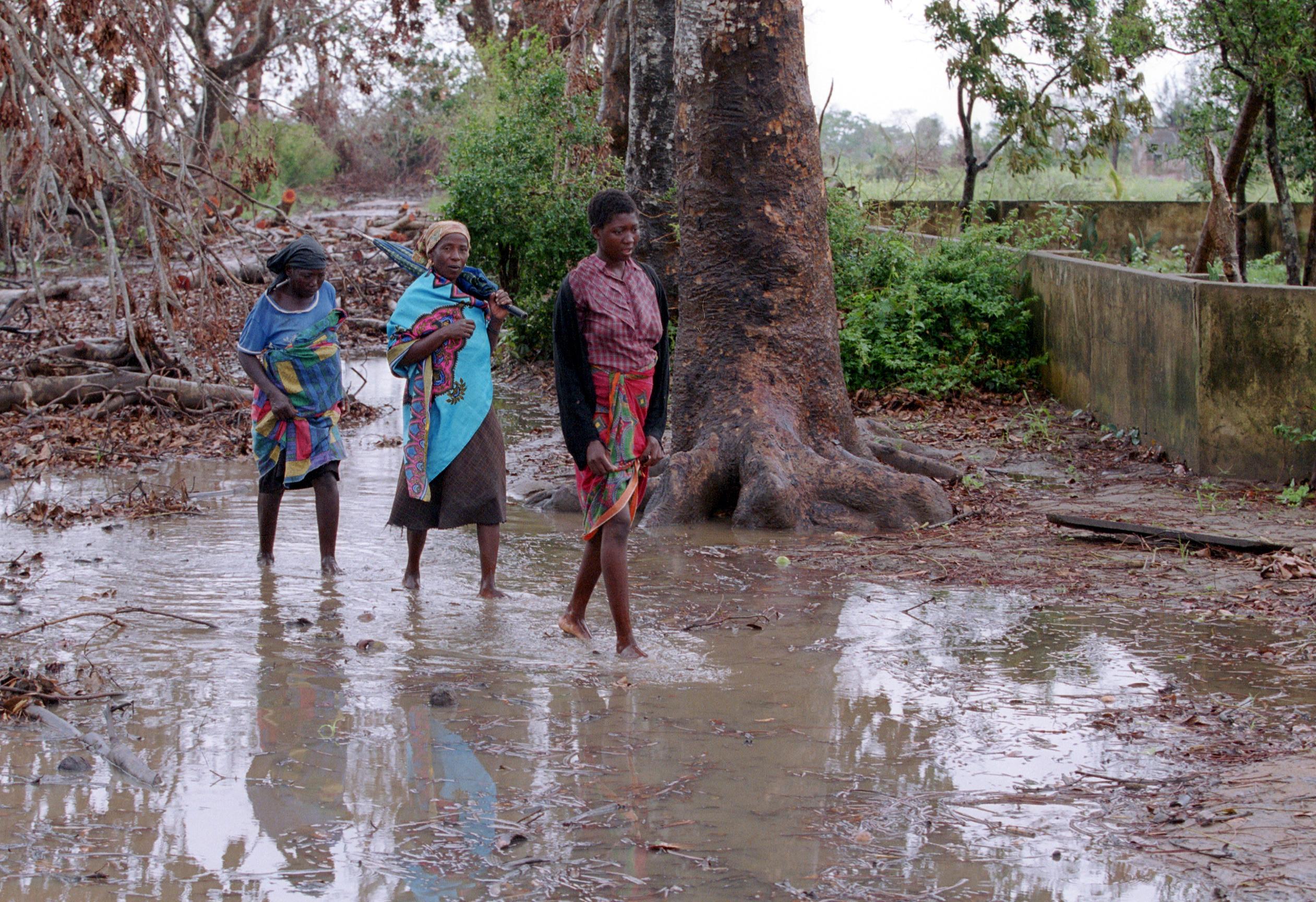 Überschwemmung in Mosambik, Frauen waten durch Wasser, dass einen Weg überflutet hat.