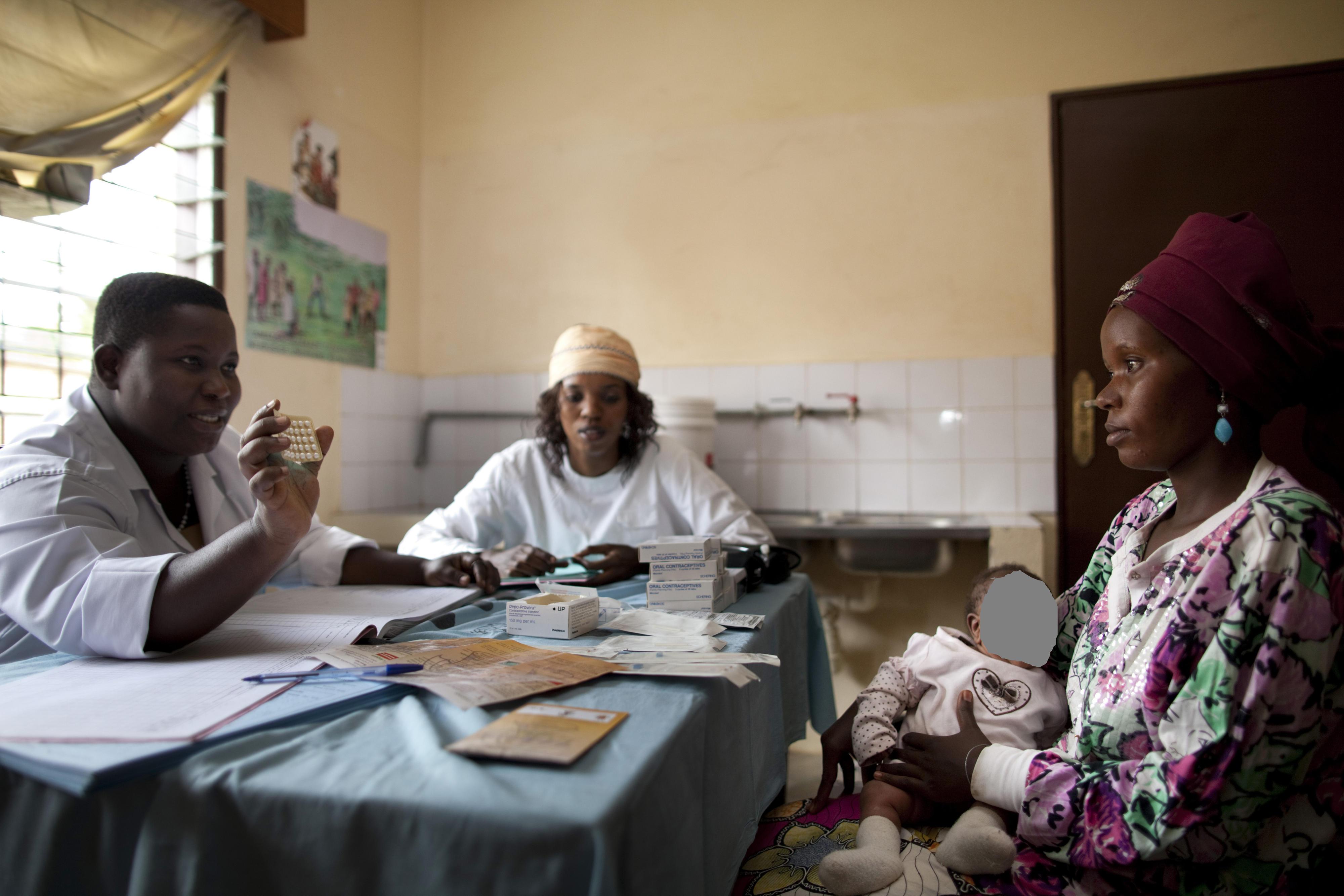 Beratung zum Thema Verhütungsmittel in einer Gesundheitsstation in Bujumbura, Burundi. Eine Frau mit einem Kind auf dem Schoß sitzt am Tisch. Ihr gegenüber sitzt eine Beraterin in einem weißen Kittel und zeigt ihr eine Tablettenpackung.