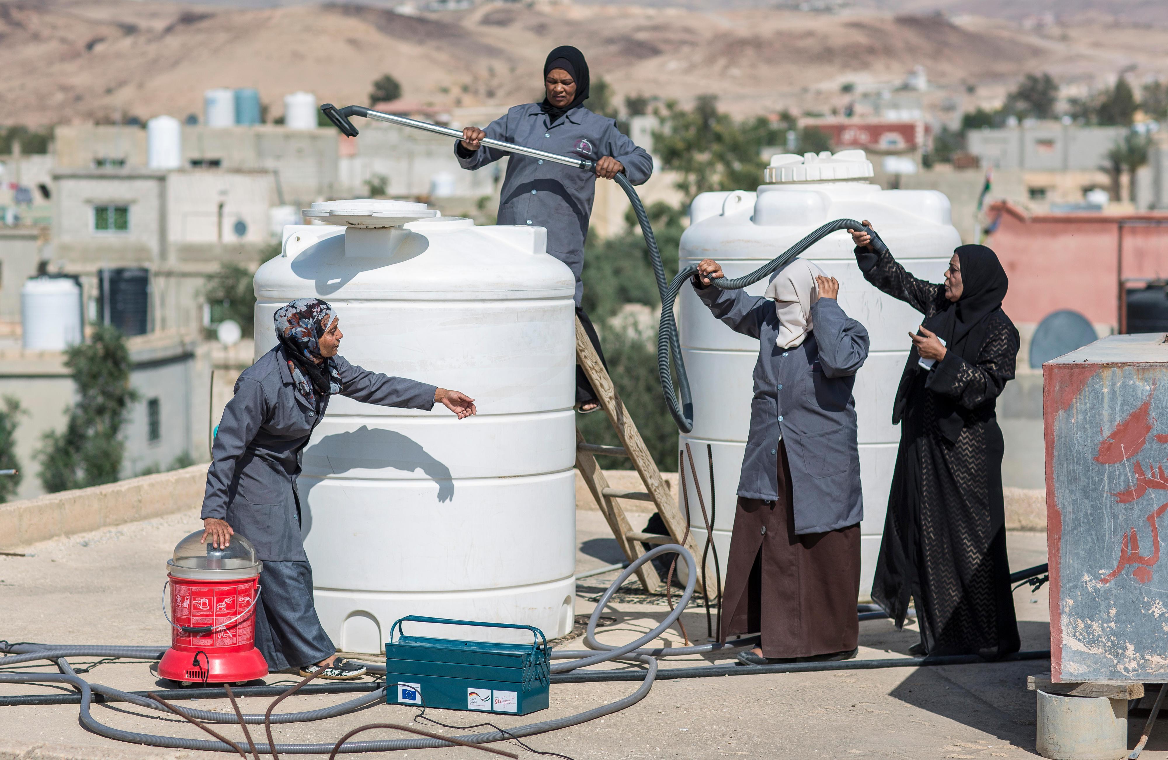 """Frauen der """"Wise Women Plumbers Cooperation"""" bei der Säuberung eines Wasserspeichers in Jordanien"""